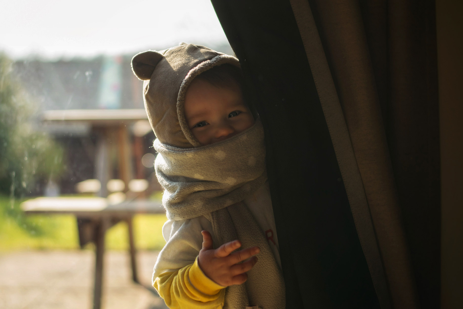 Young toddler wearing Bobo Choses mercredi stripe sweatshirt, Rockahula scarf and +1 in the family bear fleece balaclava smiling at Bluestone, Wales, holiday park