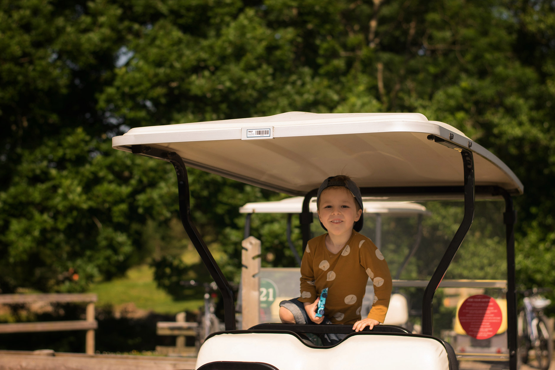 Young boy wearing Tiny Cottons faces t-shirt on golf buggy at Bluestone, Wales