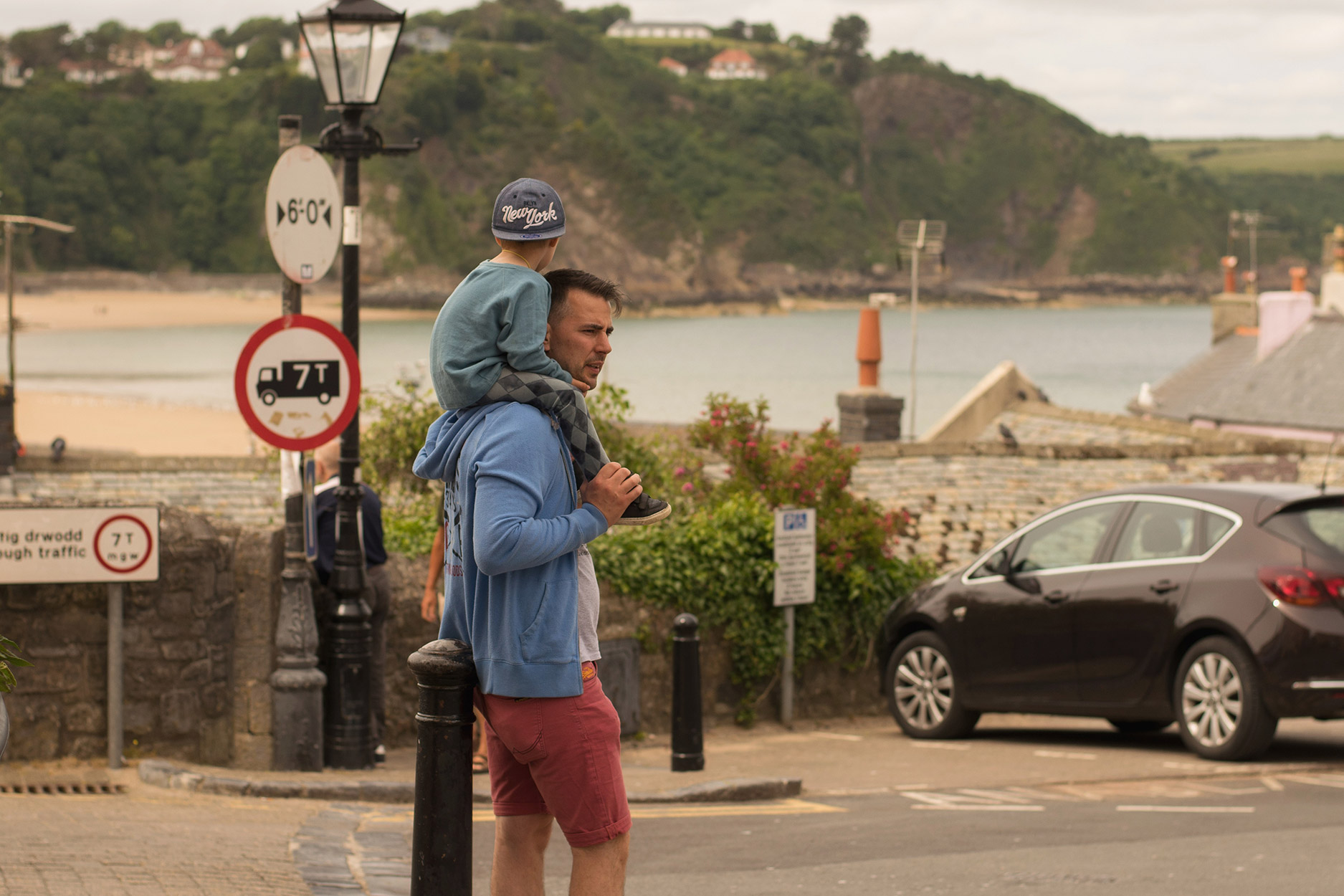 Father with young son on his shoulders amongst the landscape beaches of Tenby, South Wales