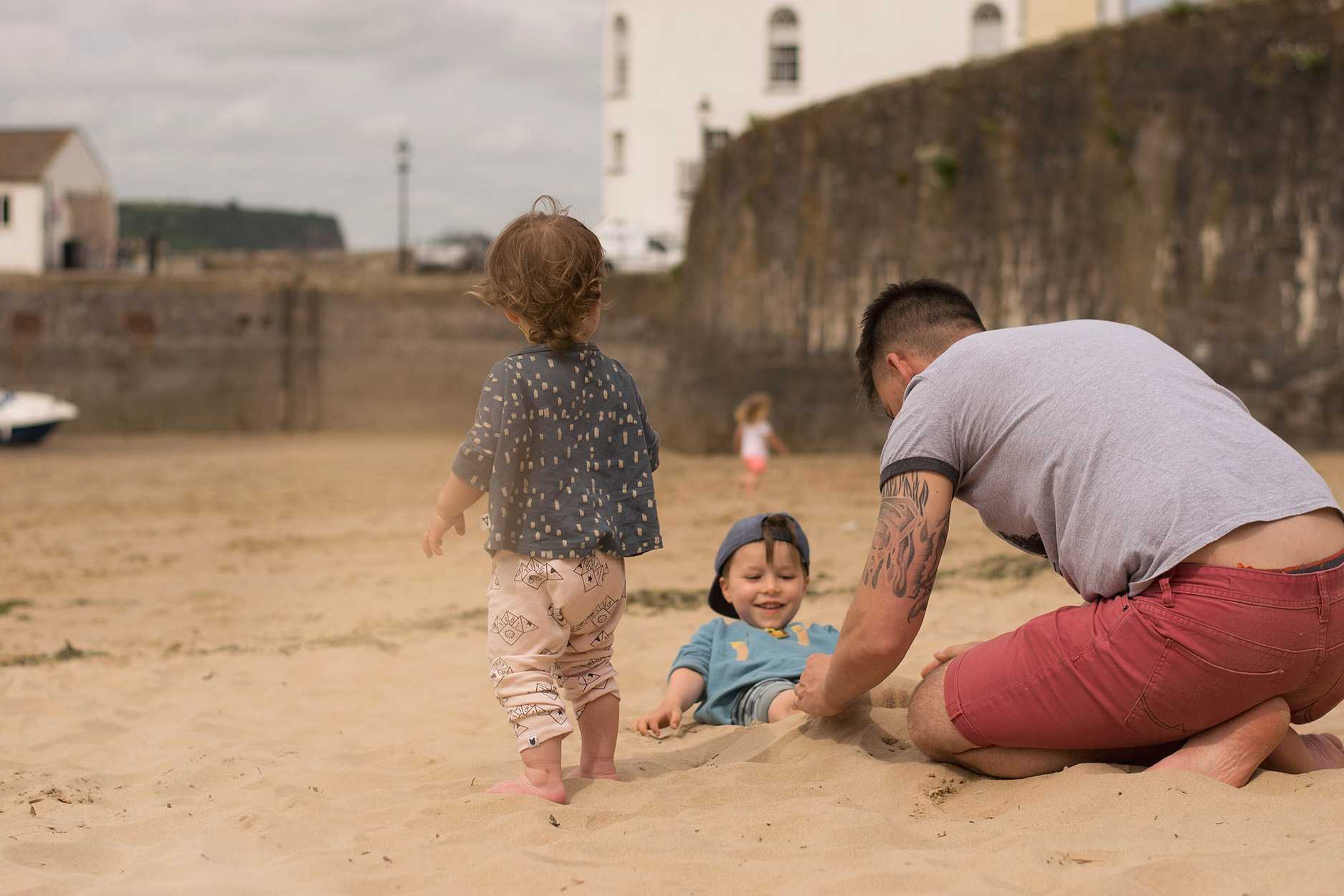 Young boy wearing Tobias and the Bear and Mr Wolf luna top on the beaches of Tenby, South Wales