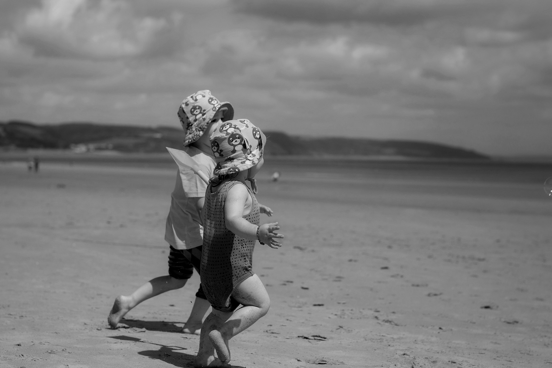 Brothers wearing Maxomorra seal sunhat racing along the beach together at Saundersfoot, South Wales