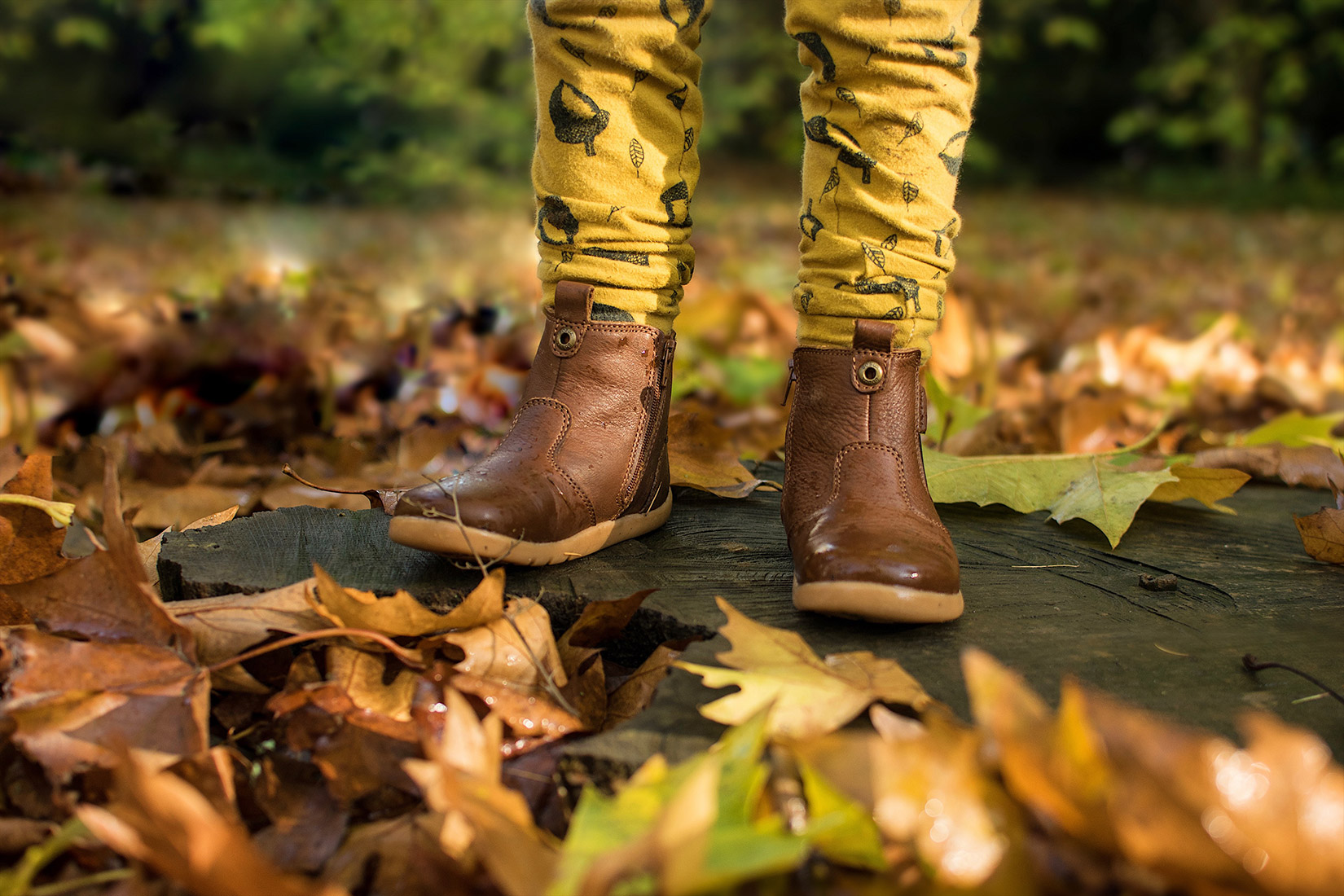 Two young brothers wearing matching Bobux iWalk outback brown boots and /bear & Babe mustard acorn leggings walking around Westonbirt Arboretum, Gloucestershire, in Autumn with family