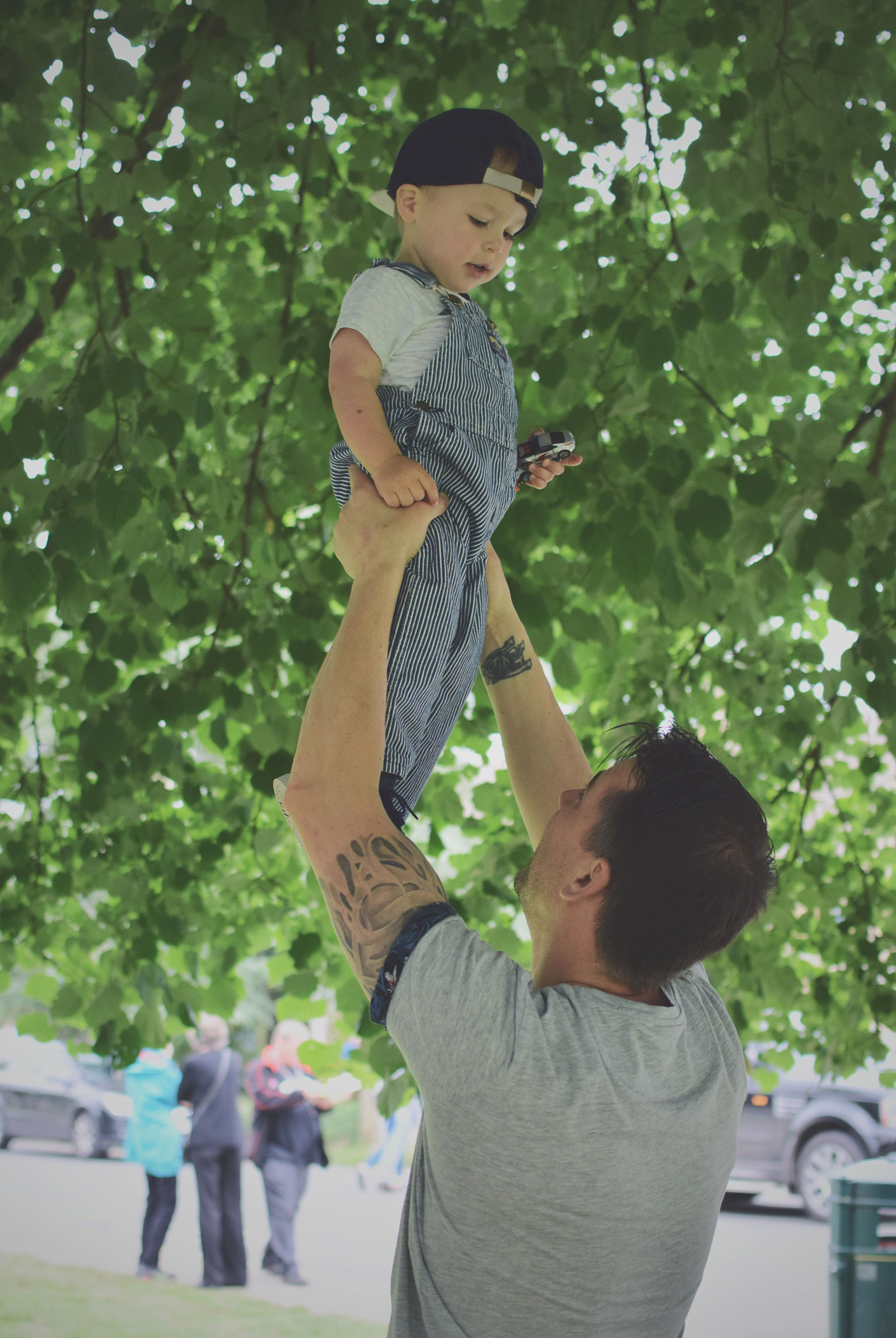 Celebrating the Daddies at Bourton-on-the-Water - Daddy holding toddler son in the air under a tree at Bourton-on-the-Water, Cotswolds