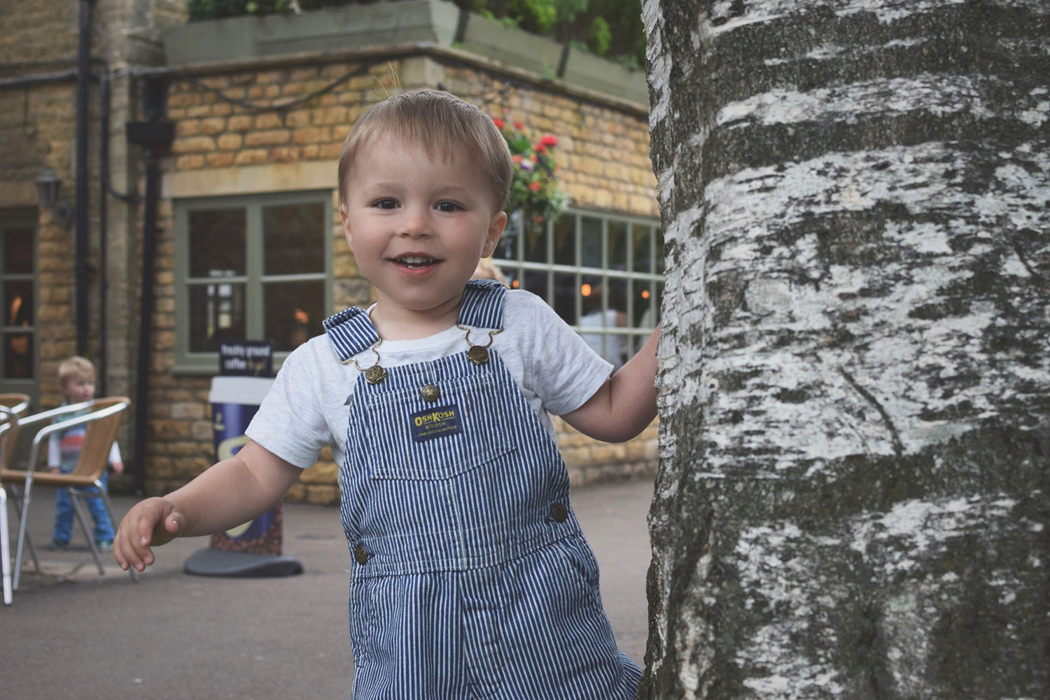Celebrating the Daddies at Bourton-on-the-Water - Toddler boy posing happily next to tree wearing H&M ledge hate and Osh-Kosh stripy blue dungarees at Bourton-on-the-Water, Cotswolds
