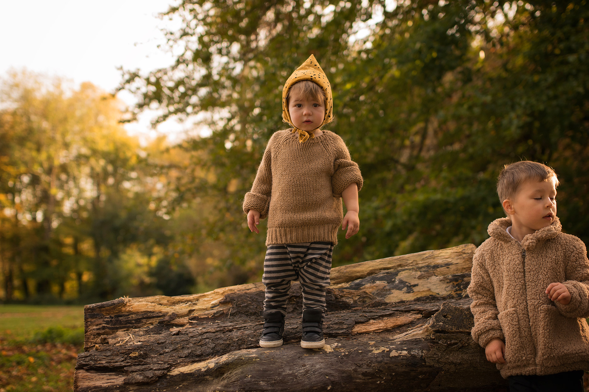 Two brothers wearing Made for Mini Good Gila hat, Mingo jumper, One More in the Family striped harems and Rylee and Cru faux fur coat playing outdoors at the park in Autumn