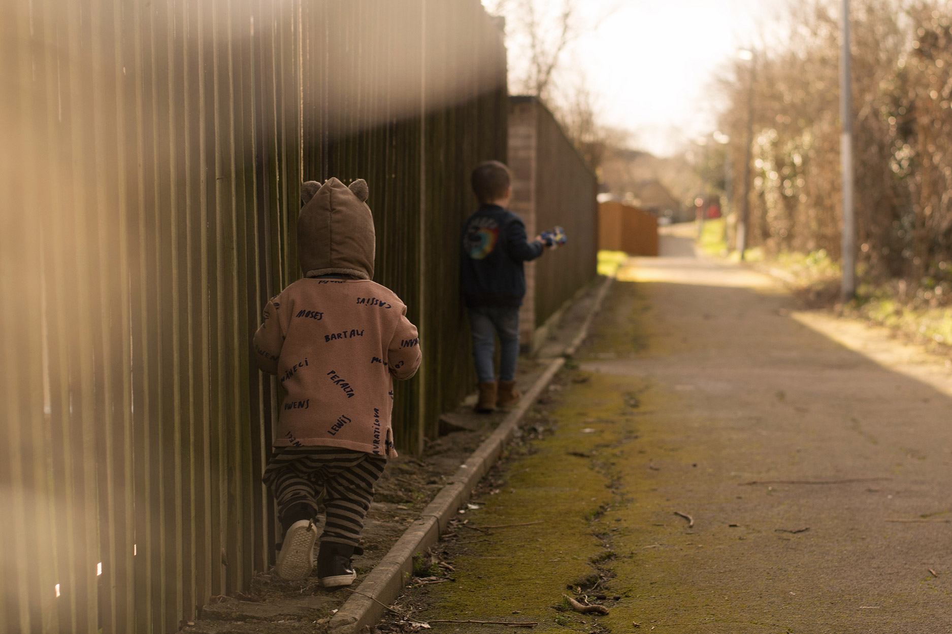 Two young brothers, on a sunny Winter walk wearing The Bonnie Mob denim rainbow jacket and blue t-shirt, +1 in the Family baby bear balaclava, striped harem trousers and Bobo Choses dusky pink cardigan