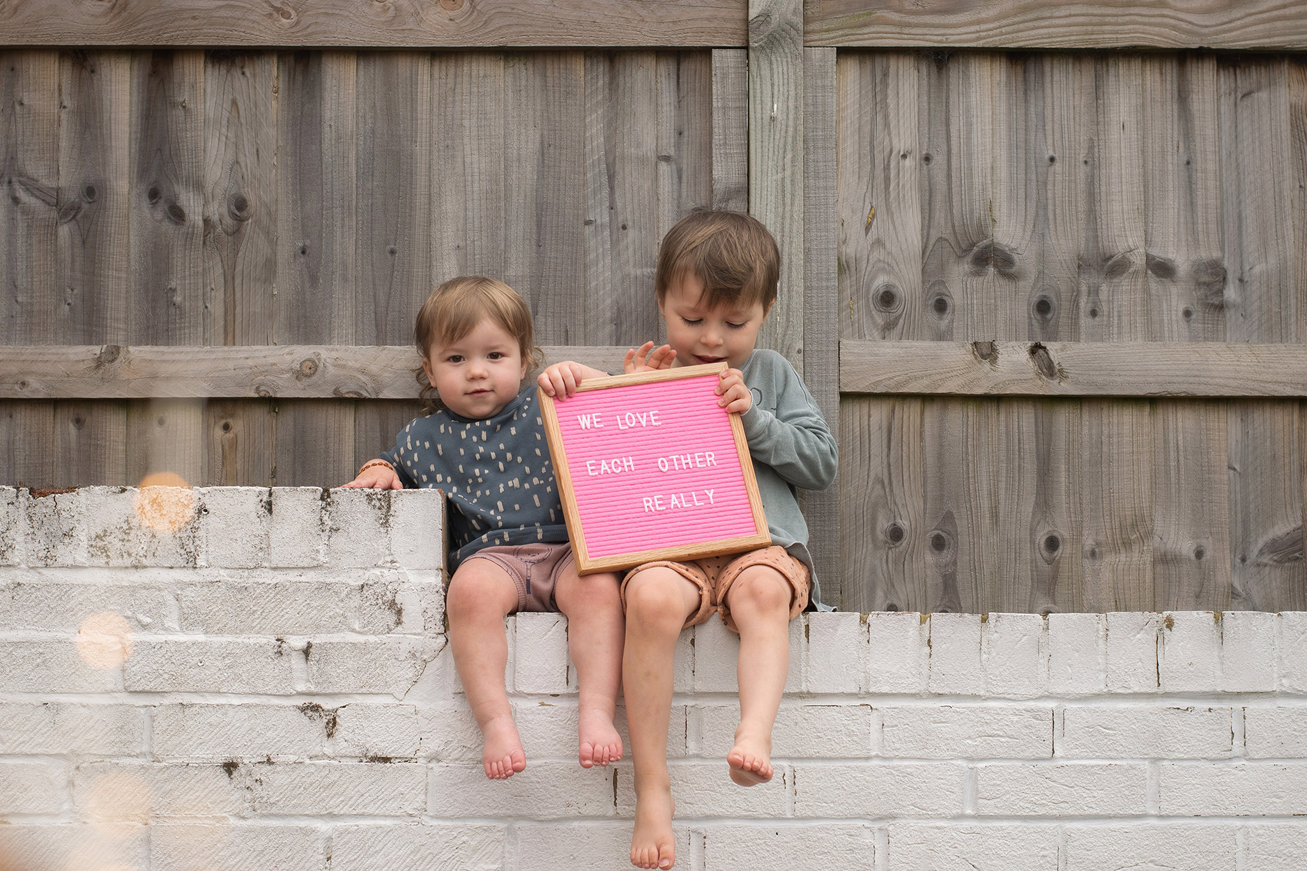 Two young brothers sitting on the wall holding a pink letter board wearing Mr Wolf luna top, Made for Mini shorts and Bobo Choses mountain top