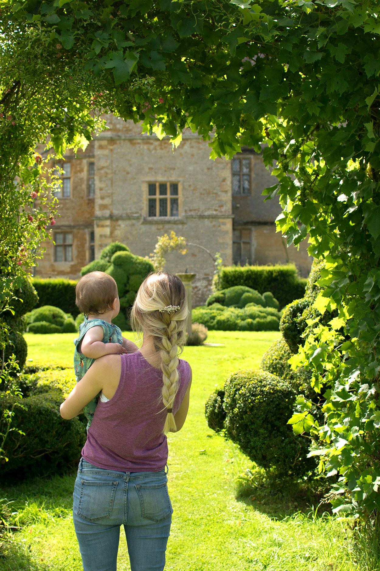 Mother and baby boy standing in the gardens wearing Mamas and Papas romper with french braided hair at Chastleton House, Oxfordshire, National Trust