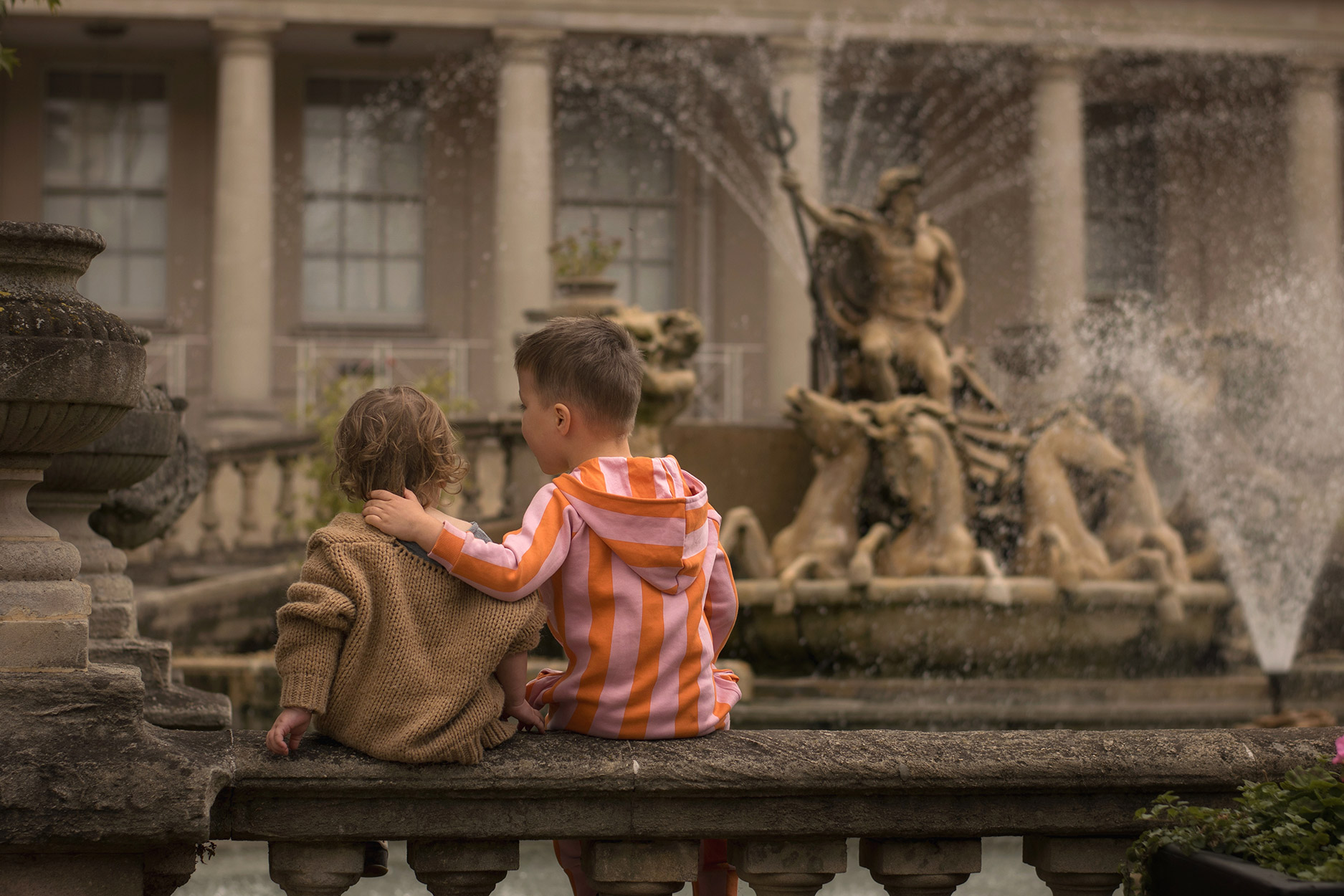 Two boys wearing Mango, Maed for Mini and Hugo Loves Tiki sitting watching the Neptune fountain in Cheltenham town centre