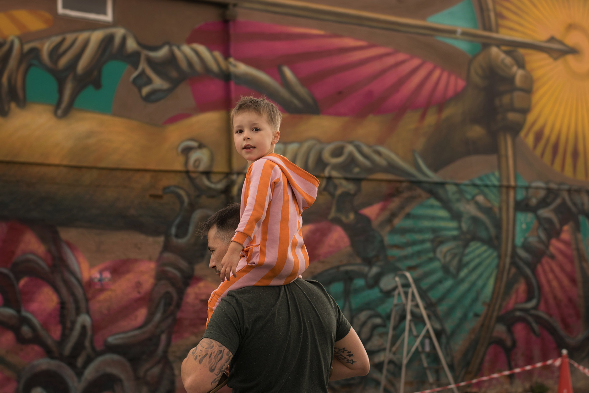 Looking around Cheltenham town centre for street art created for the paint festival 2018 - boy wearing striped Hugo Loves Tiki onesie