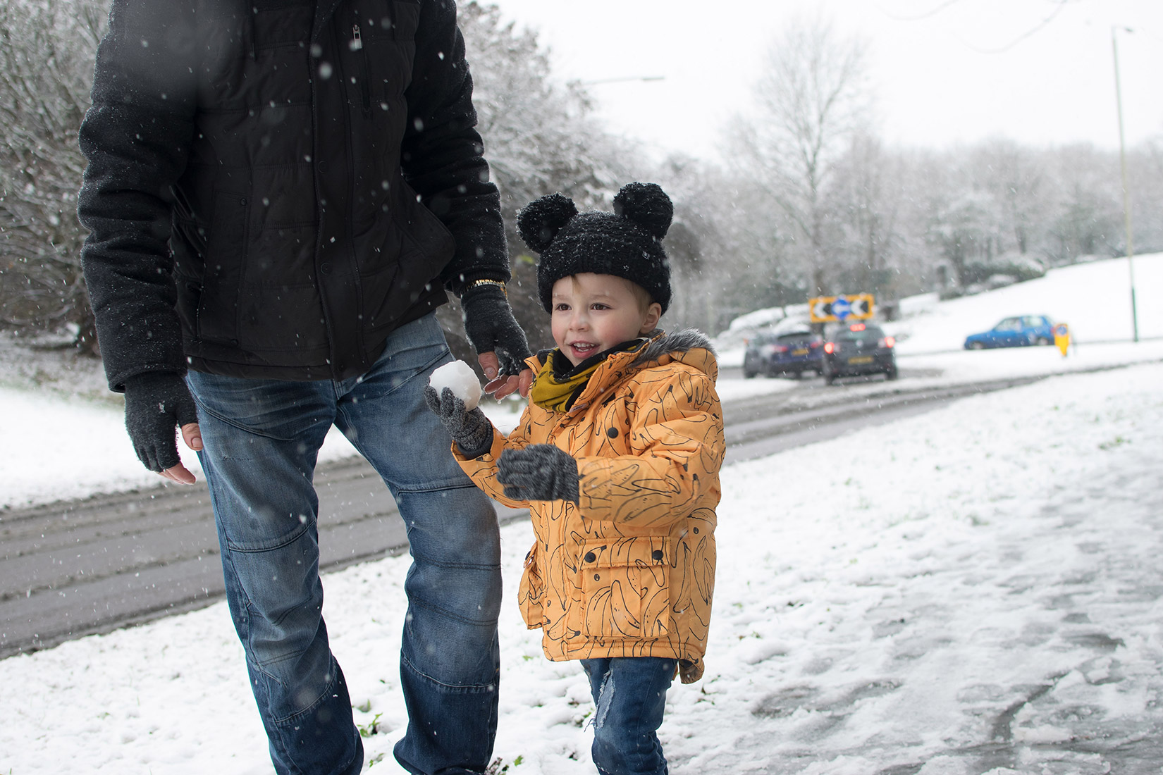 Young boy wearing Individual banana coat getting ready to throw a snowball at his Grandad