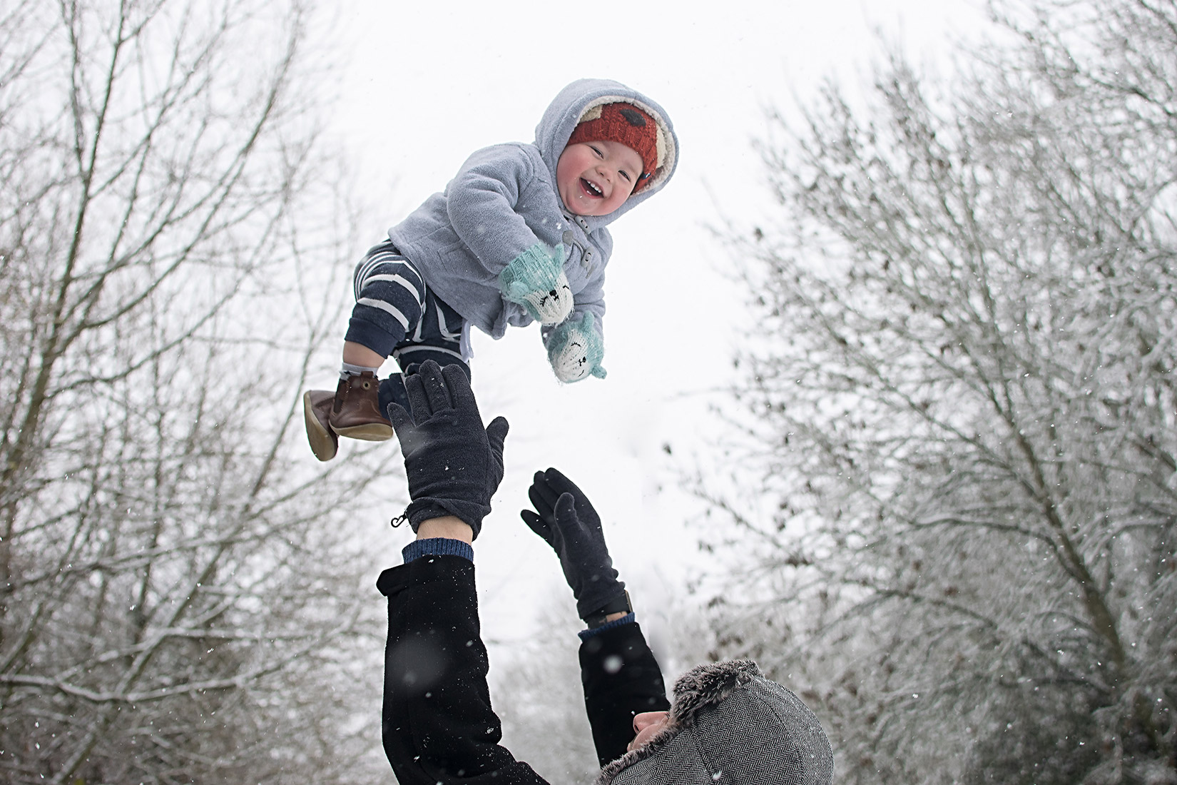 Father holding up smiling baby boy into the first snow of the year in Wiltshire, South West England, UK