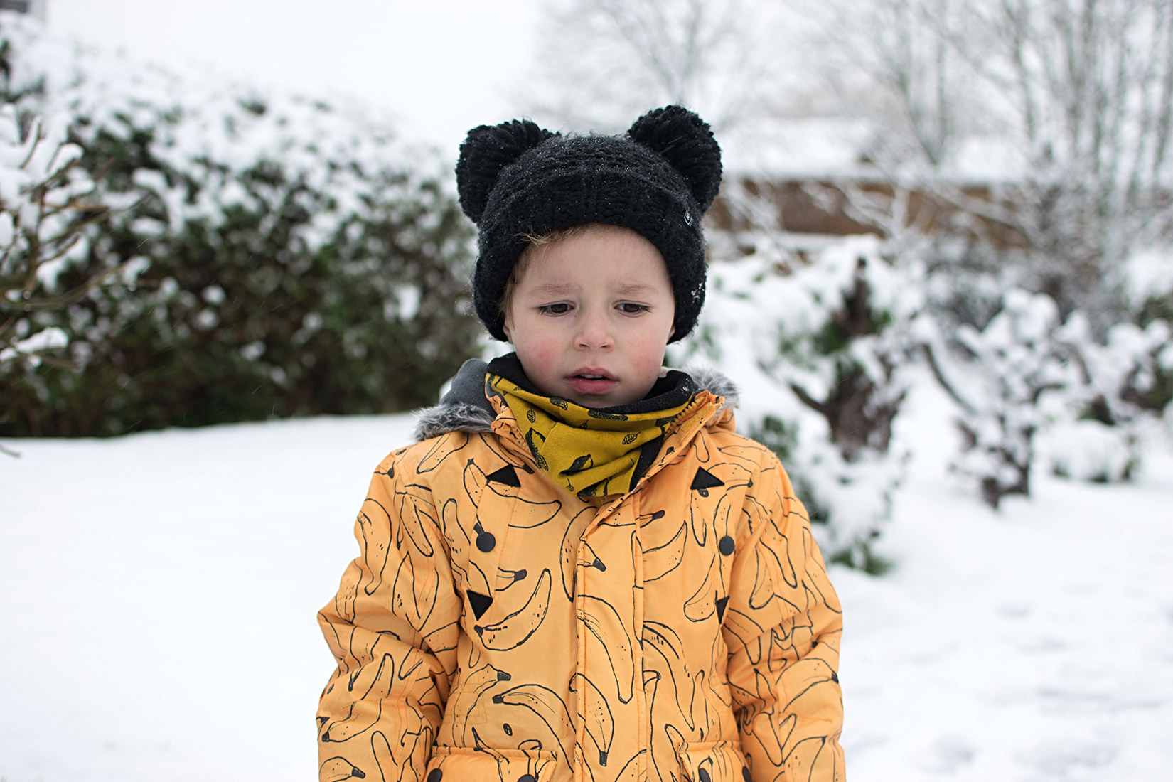 Young boy wearing Indikidual banana print parka coat and MyK by Myleene Klass black woolly hat walking along in the first snowfall of the year in Wiltshire, UK