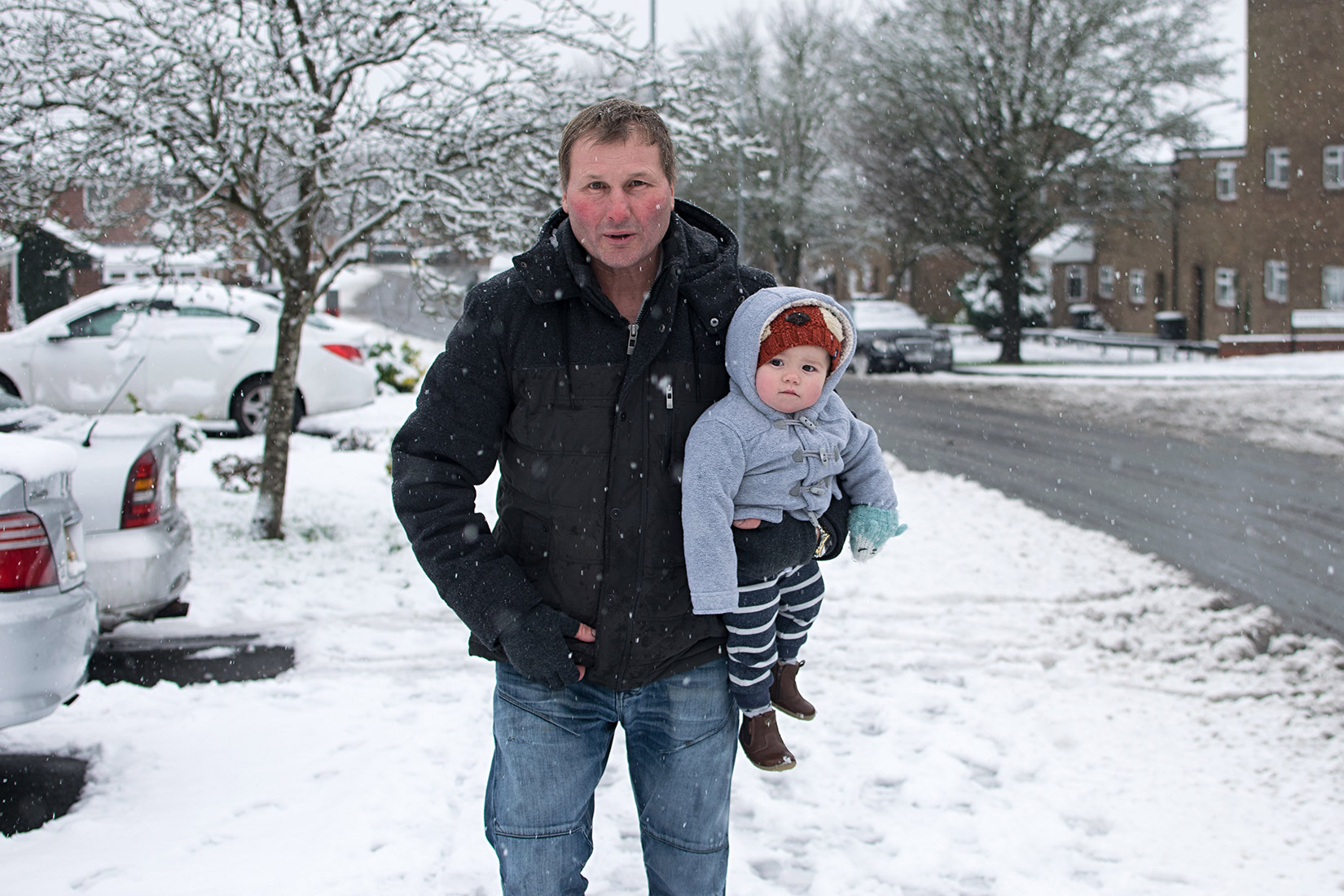 Grandad walking along in the first snowfall of the year holding young toddler grandson