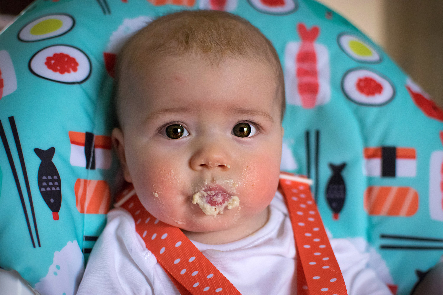50 days of weaning with Cosatto - 7 month old baby boy sitting in his Cosatto 3sixti2 highchair in chopsticks eating porridge