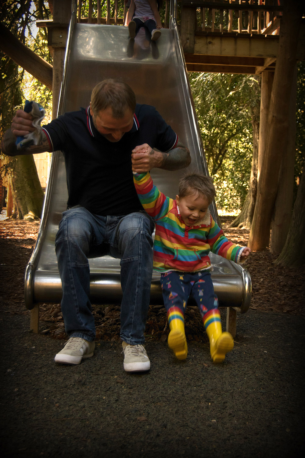 Grandad and grandson on the slide at Cotswold Wildlife Park with family