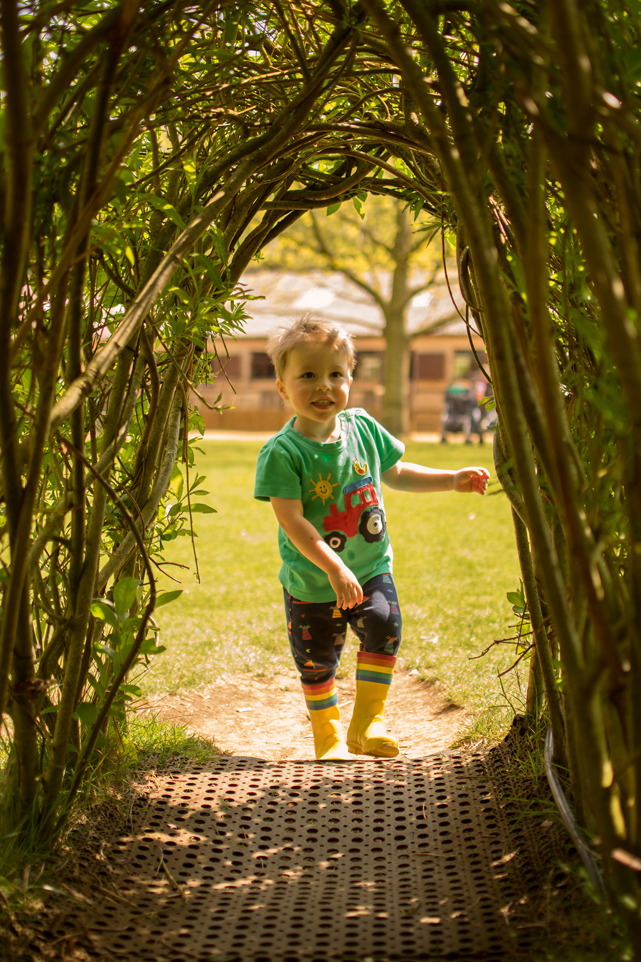 3 year old pre-schooler running through the tree den at the farm wearing Frugi tractor t-shirt and bottoms at Cotswold Wildlife Park with family