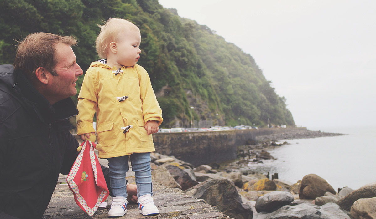 Our Devon Holiday 2015 - Toddler wearing George yellow mac looking out to sea with Grandad