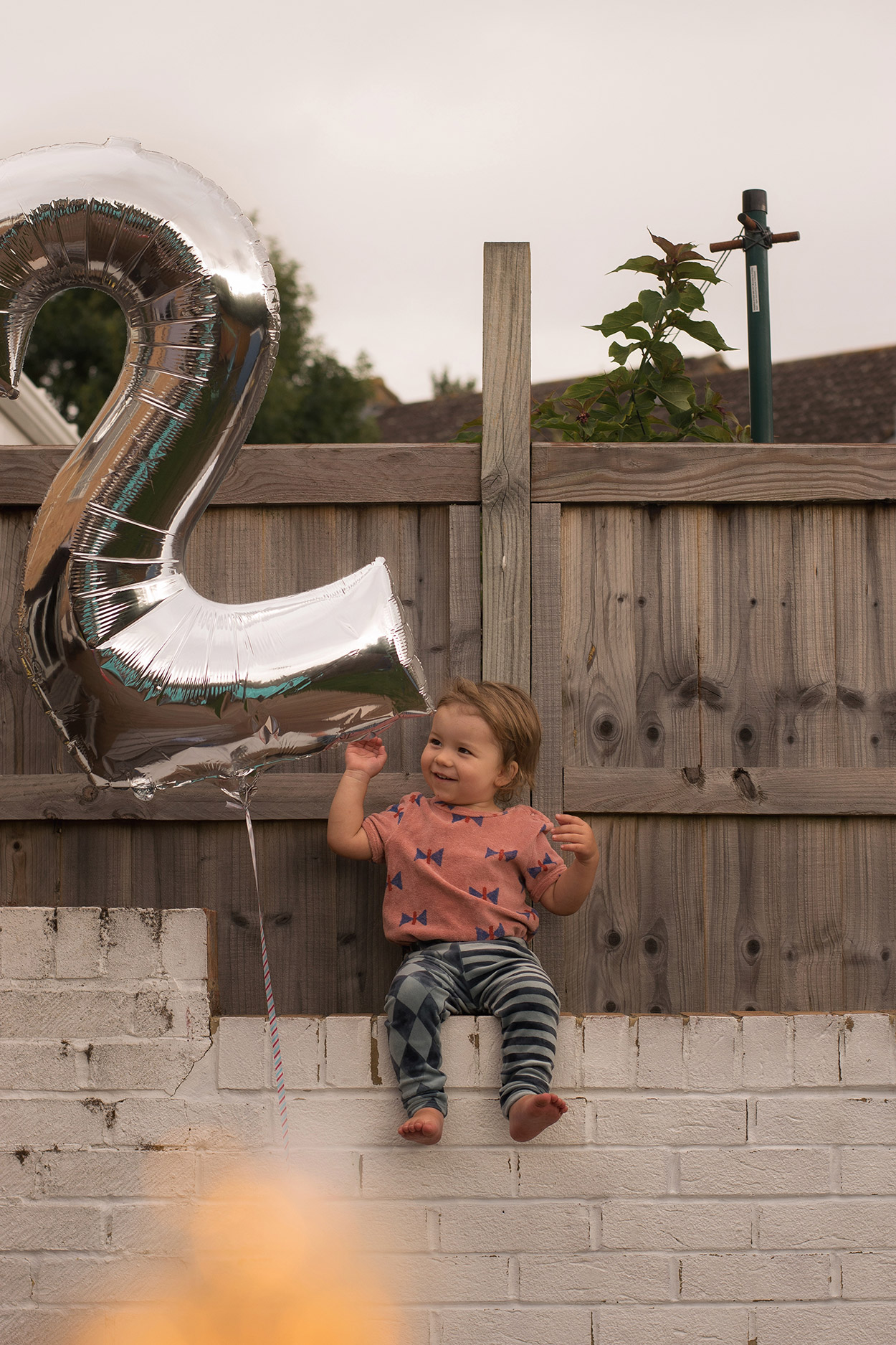 Toddler wearing Bobo Choses butterfly vest and H&M carnival leggings holding number two birthday balloon outdoors