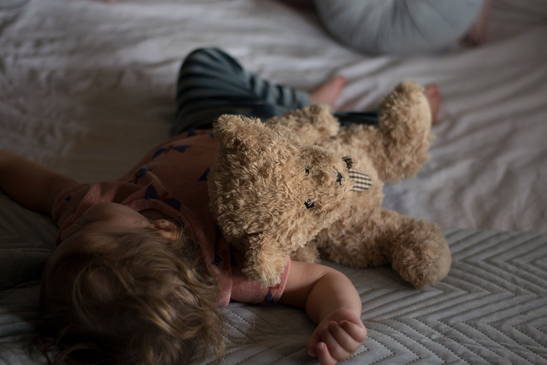 Toddler having a nap with teddy bear wearing Bobo Choses butterfly vest