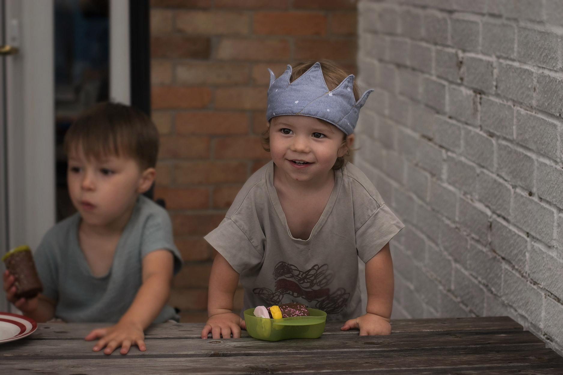 Toddler wearing JOHN Bobo Choses t-shirt and fabric birthday crown at tea party with grandparents and family