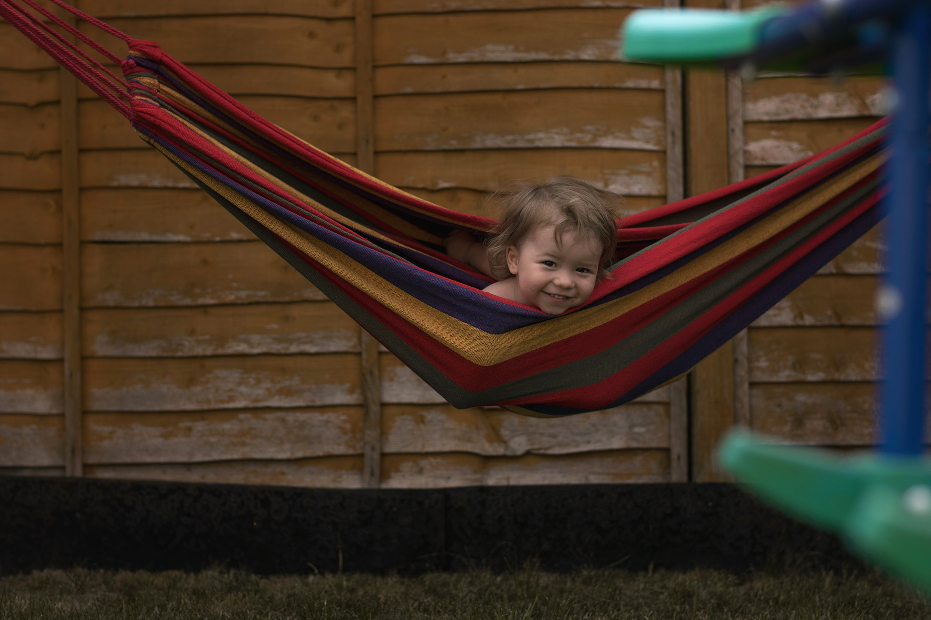 Toddler having fun and playing in hammock in the garden