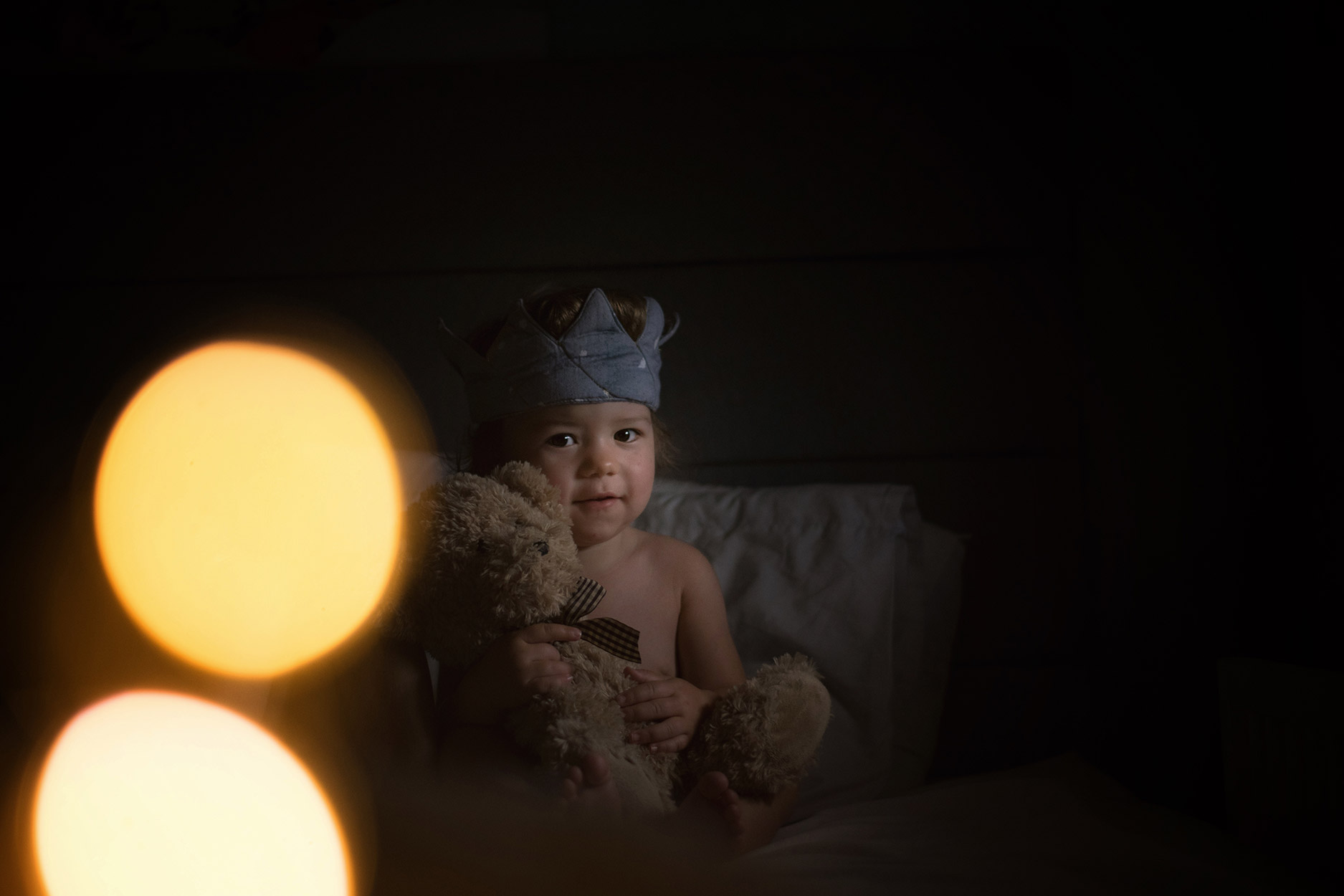 Toddler waking up in the morning of his second birthday wearing fabric crown in bed holding teddy bear