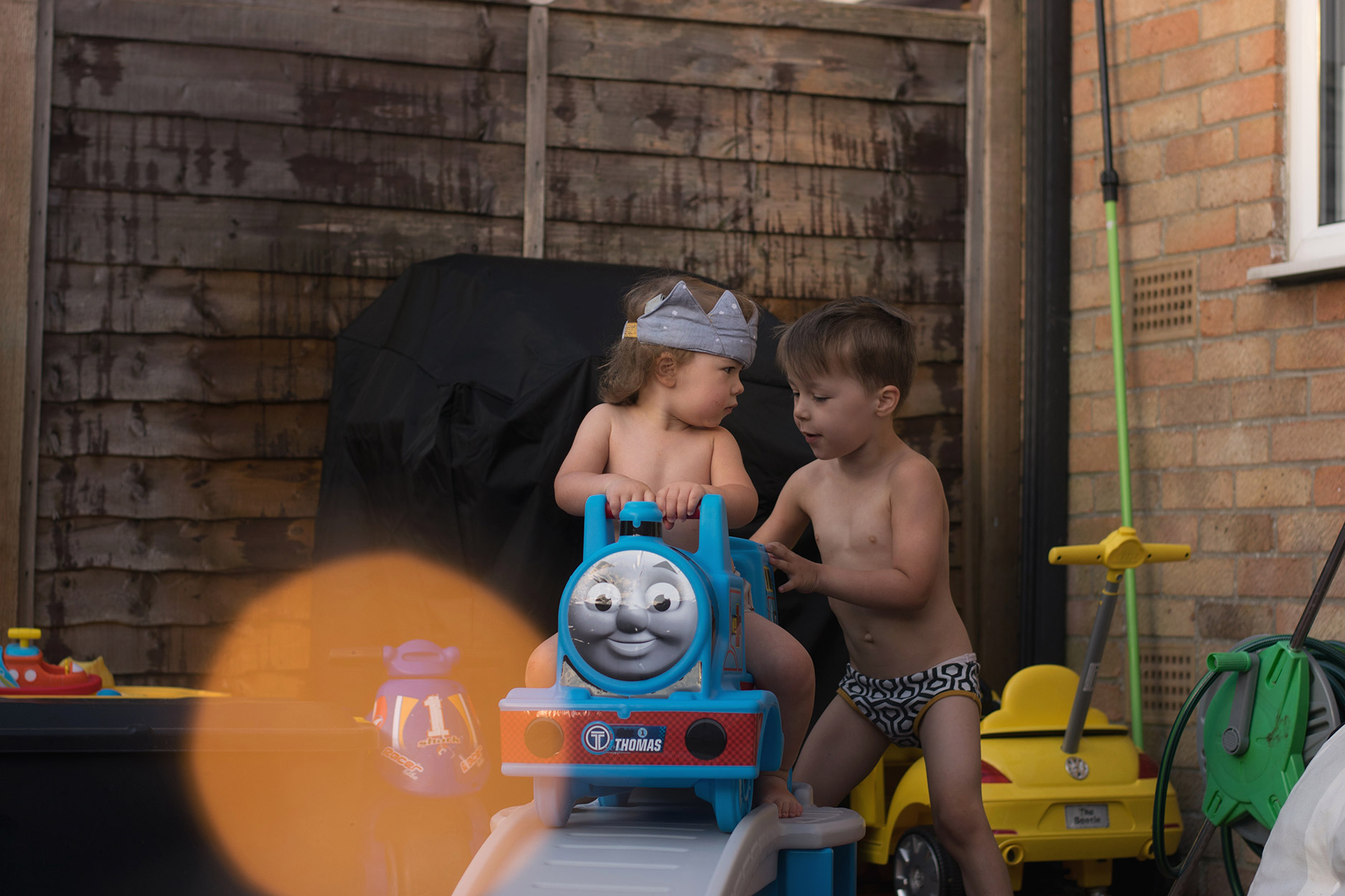 Toddler playing on Thomas the Tank Engine rollercoaster toy wearing fabric crown on birthday