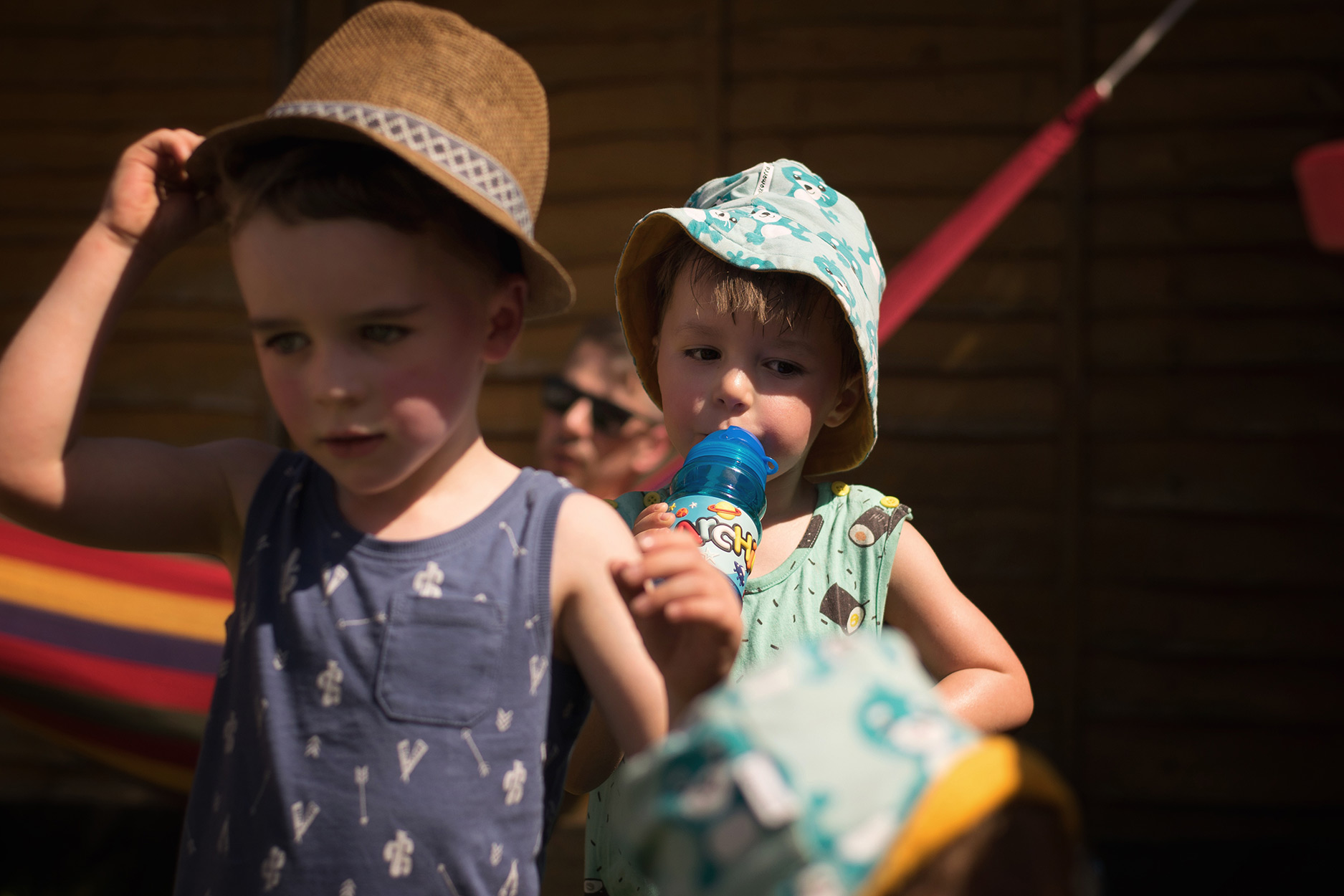 Young cousins playing together in the sun, wearing sunhat and swinging in hammocks, at Summer garden barbecue