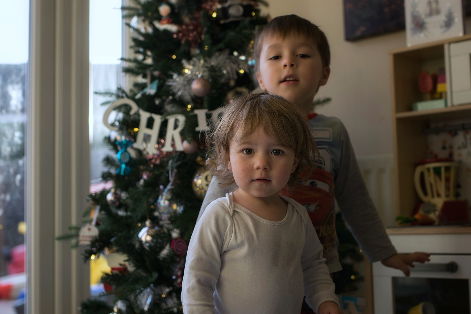 Two brothers standing in front of Christmas tree in December, cuddling and laughing, candid photography taken on Nikon D3300