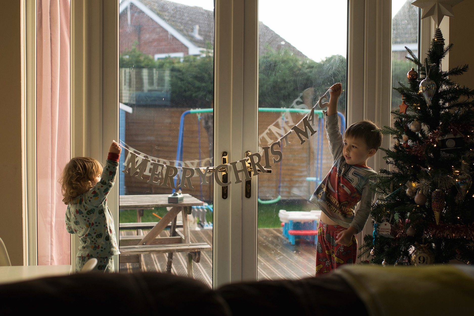 Two brothers wearing Little Green Radicals pyjamas holding up a Merry Christmas banner in living room, candid photography taken on Nikon D3300