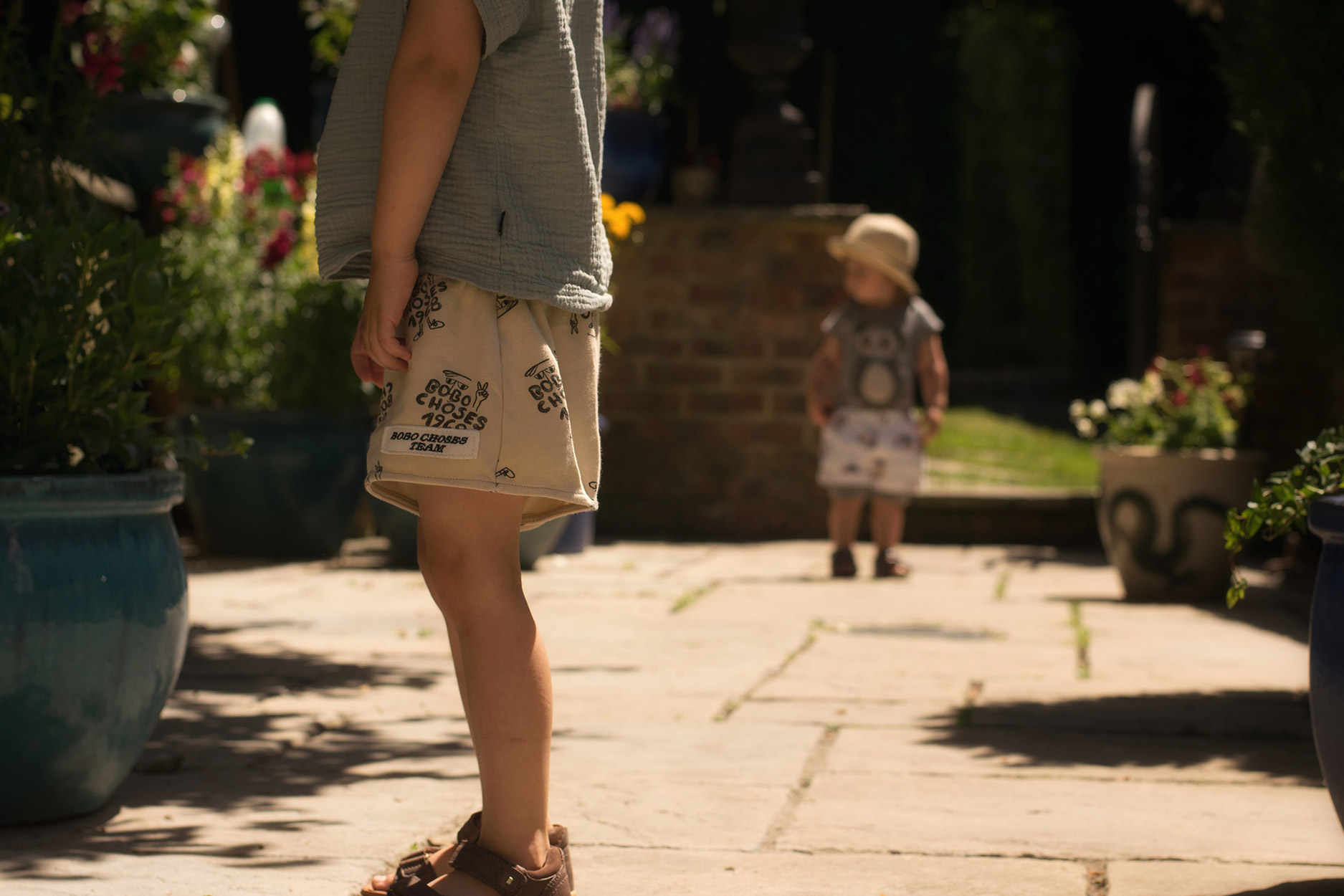 Toddler wearing Soft Gallery panda romper and Bobo Choses beach balls shorts with brother wearing Bobux sandals