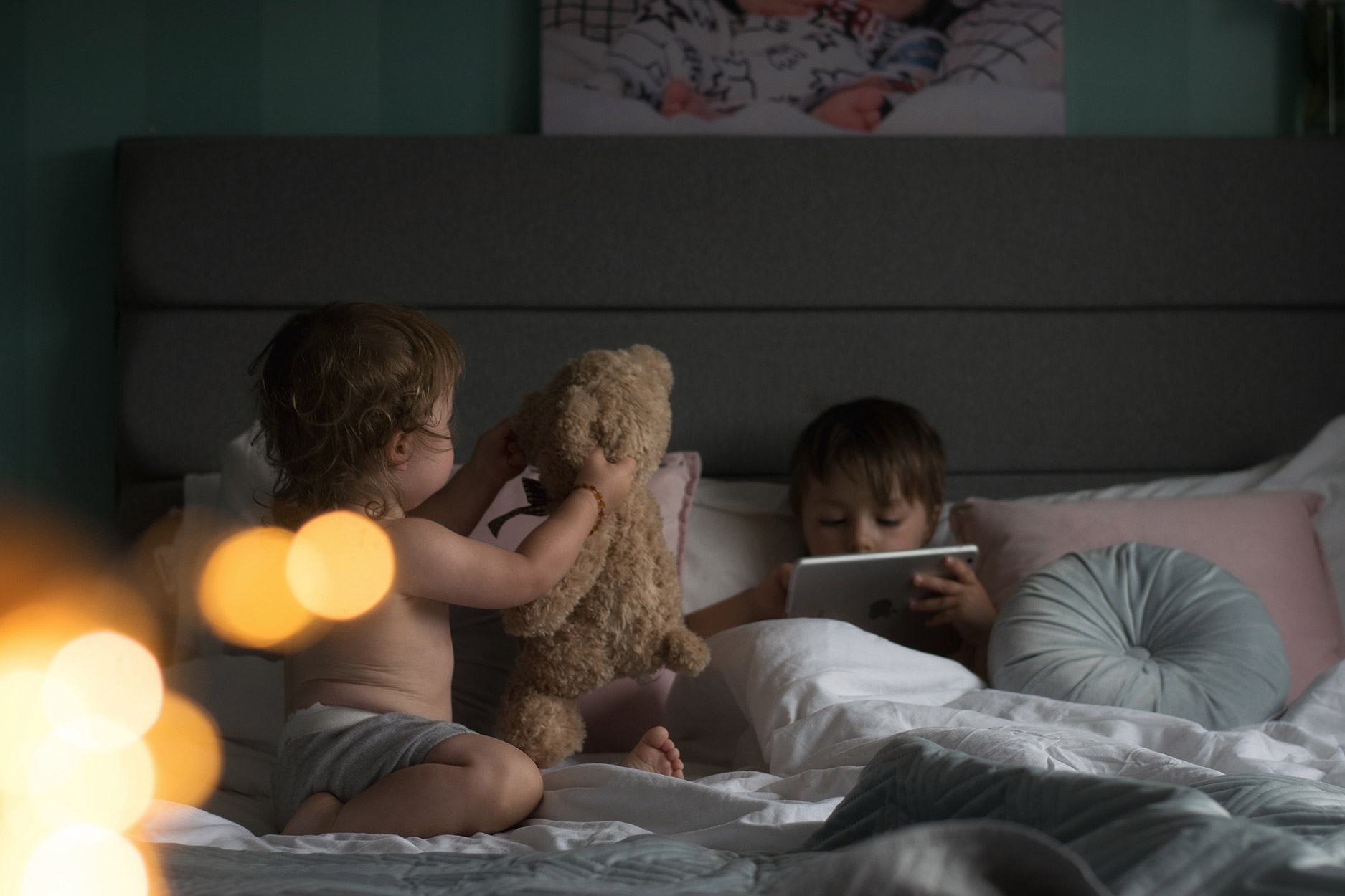 Two brothers lazing around in the morning cuddling with teddy on Dreams king-size family bed with Simba mattress