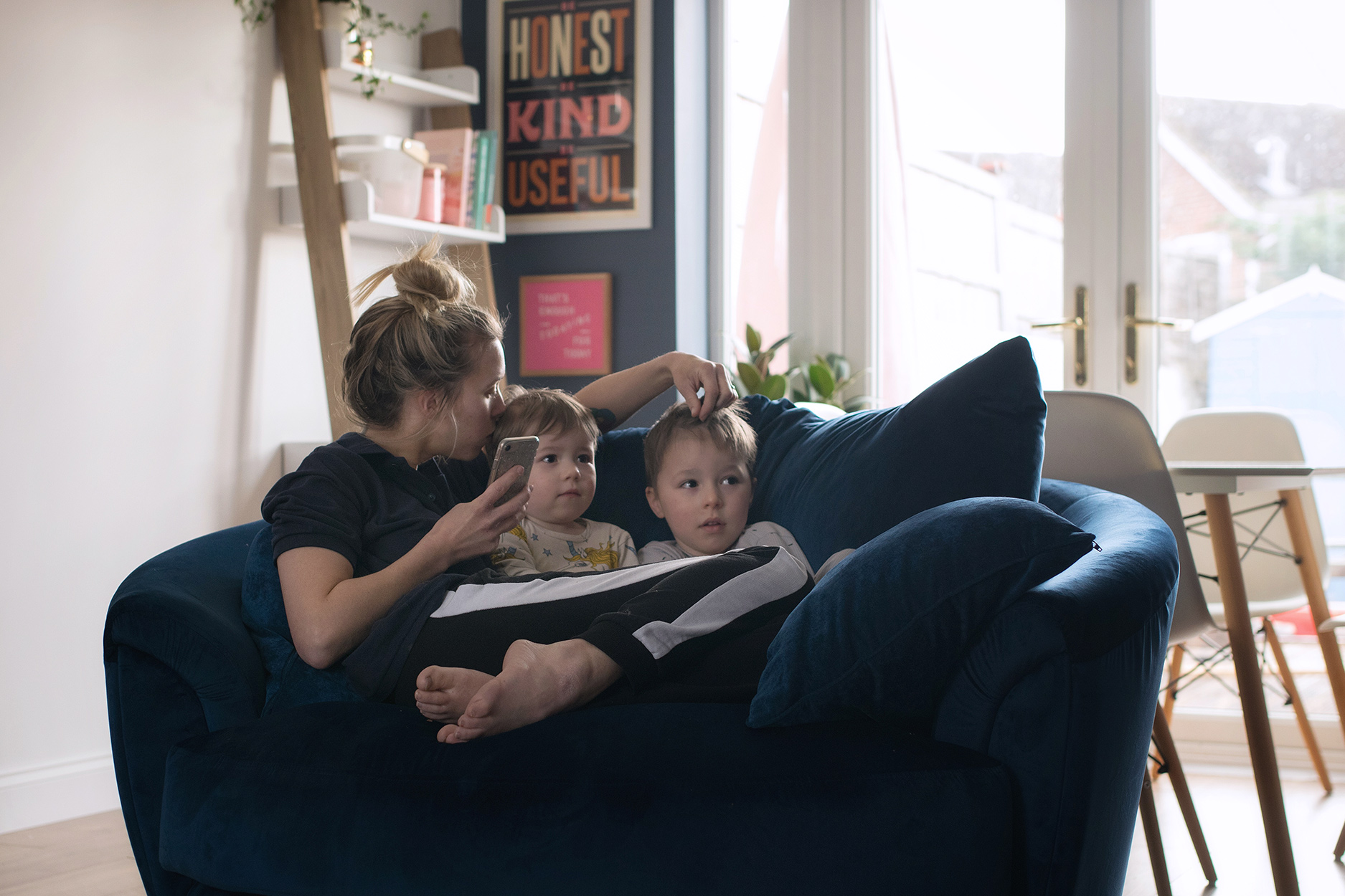 Candid family day in the life photoshoot | Recently renovated living room featuring Desenio plant wall art prints, boy sitting on royal blue velvet cuddler spinning chair wearing Zara pyjamas and Mini Rodini unicorn vest