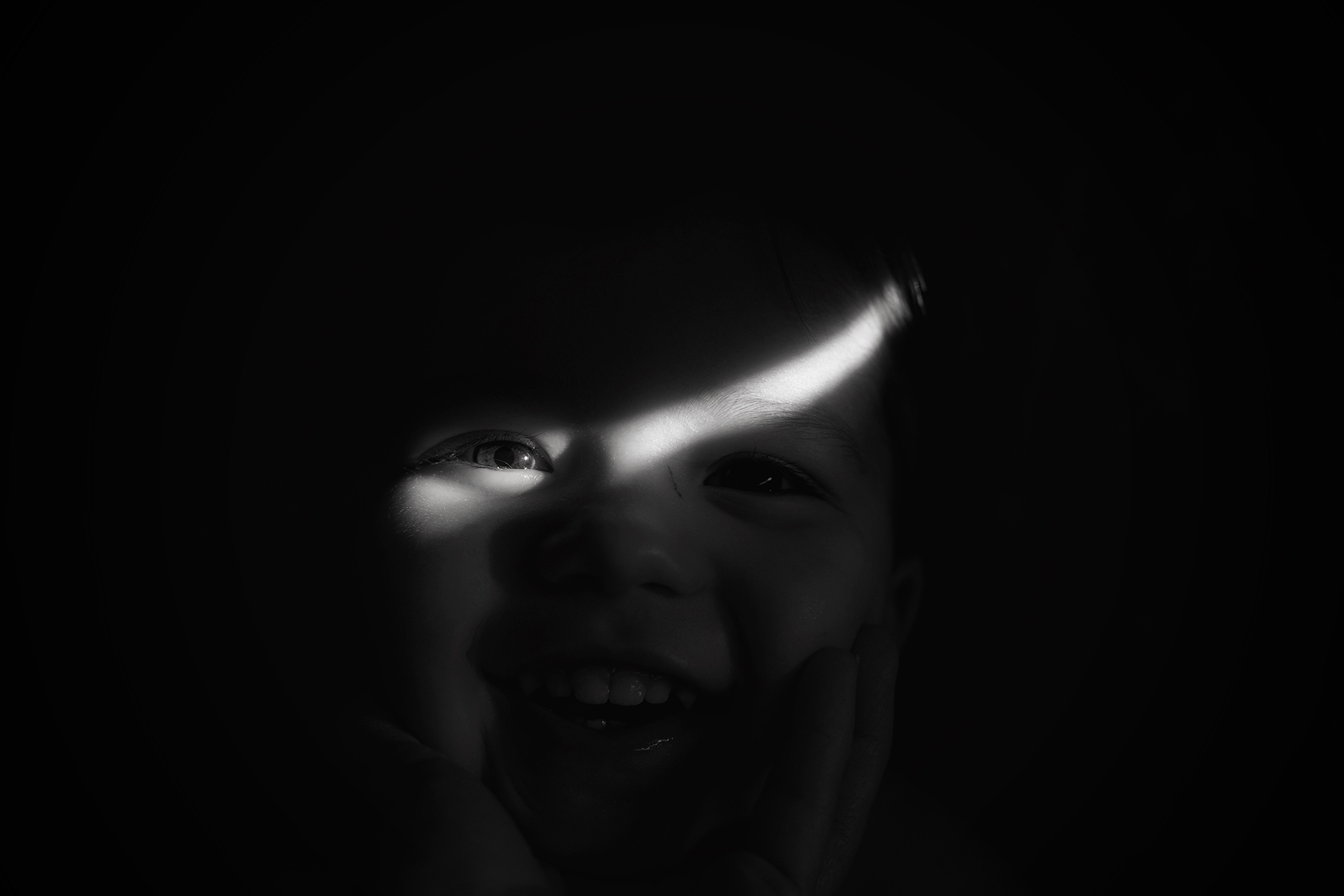Candid family day in the life photoshoot   Portrait of toddler with eye in the ray of light in morning