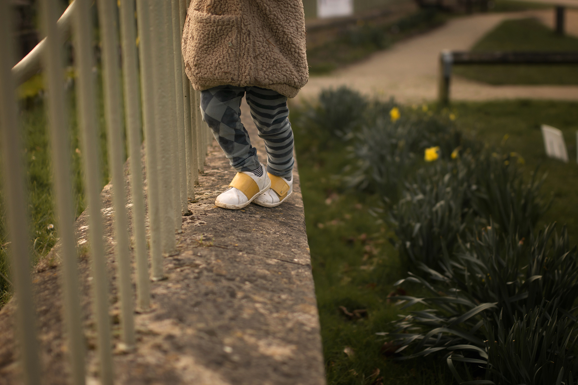 Candid family day in the life photoshoot | Toddler wearing Rylee and Cru fur coat wearing Bobux yellow stripe boston trainers climbing along wall at the park