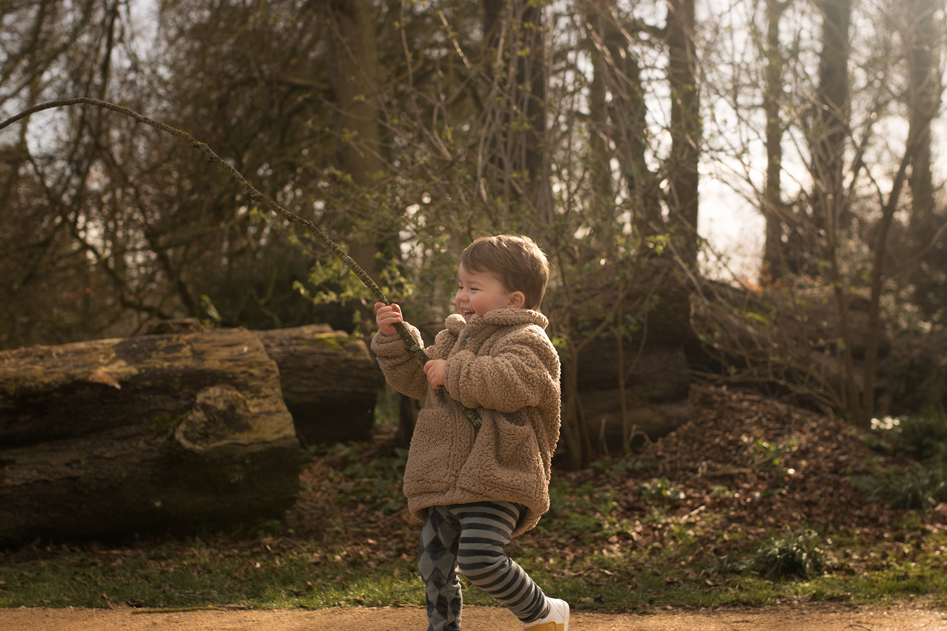 Candid family day in the life photoshoot | Toddler wearing Rylee and Cru fur coat, H&M carnival leggings and Bobux boston trainer out for woodland walk carrying stick