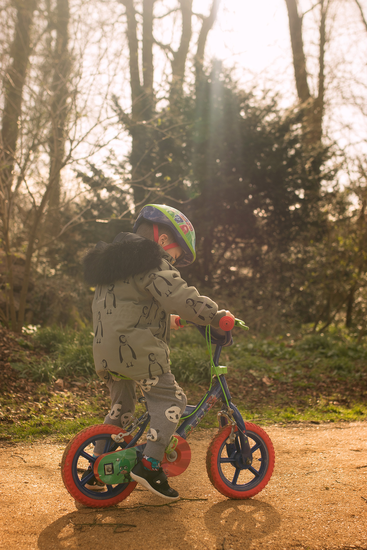 Candid family day in the life photoshoot | Boy wearing Mini Rodini K2 penguin parka and bicycle helmet riding PJ Masks bike at the park