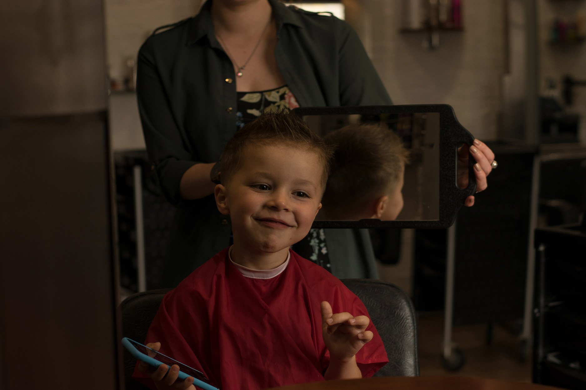 Boy looking in the mirror at hairdressers after haircut