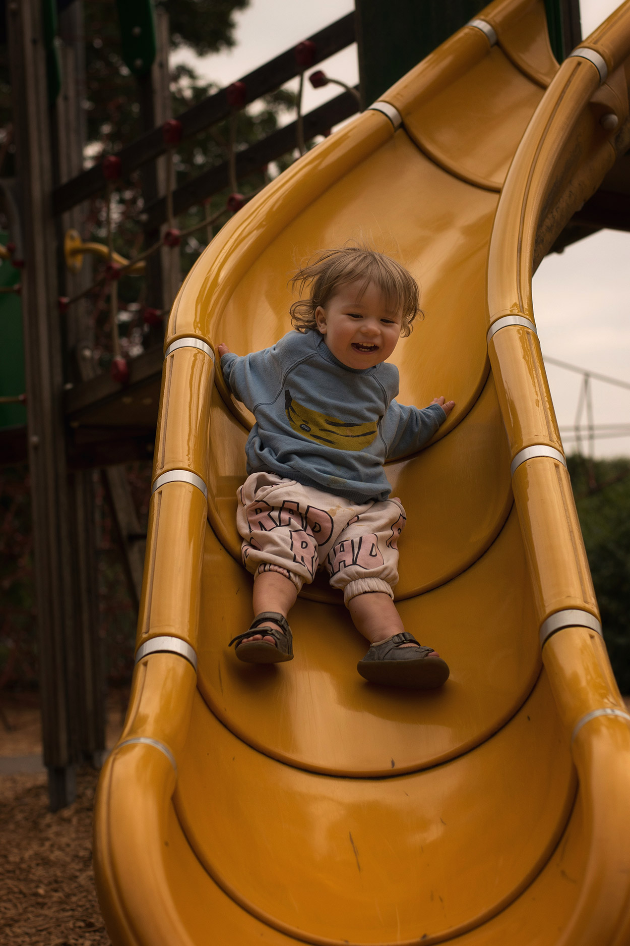 Toddler wearing Bobo Choses and Hugo Loves Tiki climbing the spiderweb at local park with family