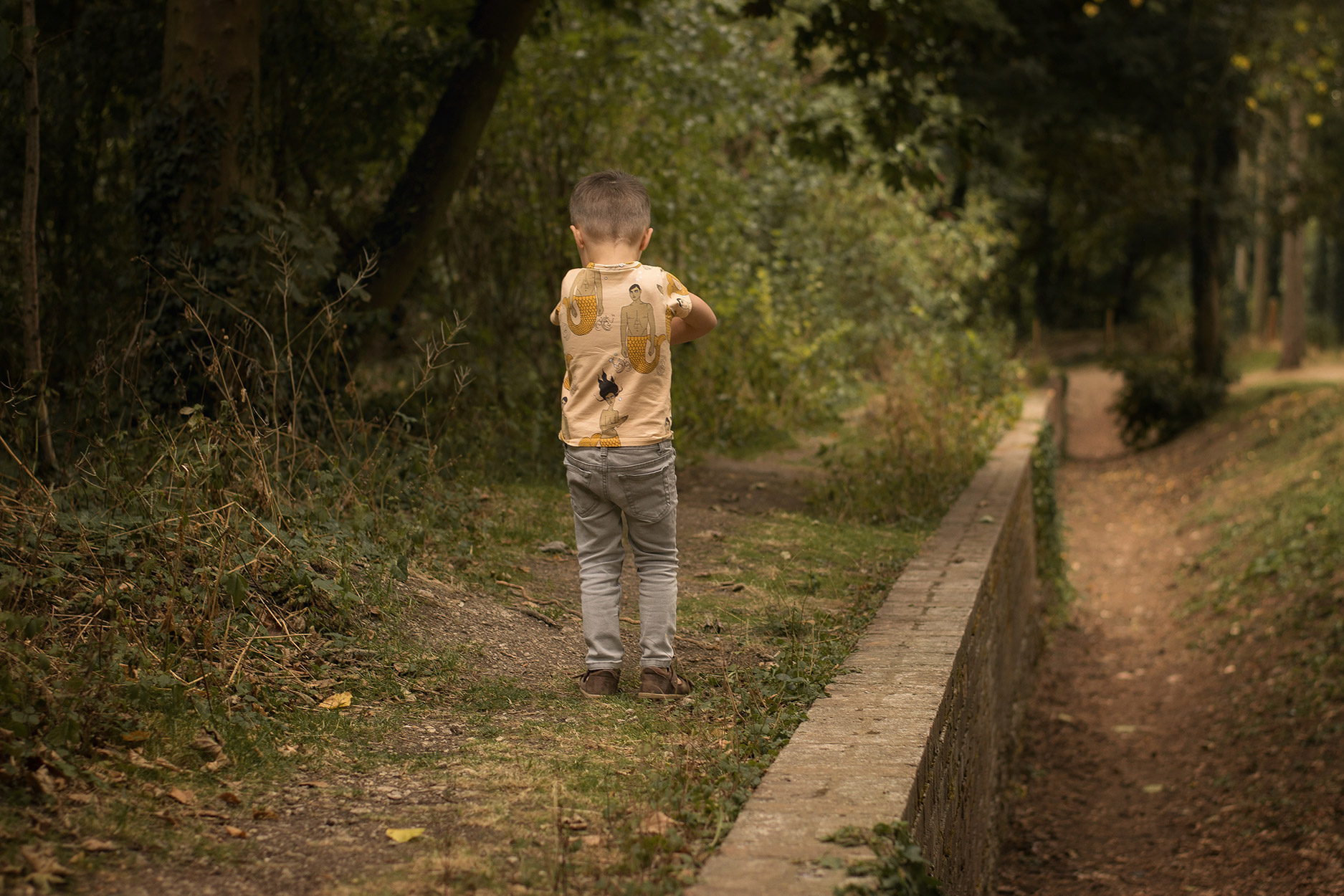 Toddler wearing Bobo Choses, Hugo Loves Tiki and Bobux walking amongst the grass at the park