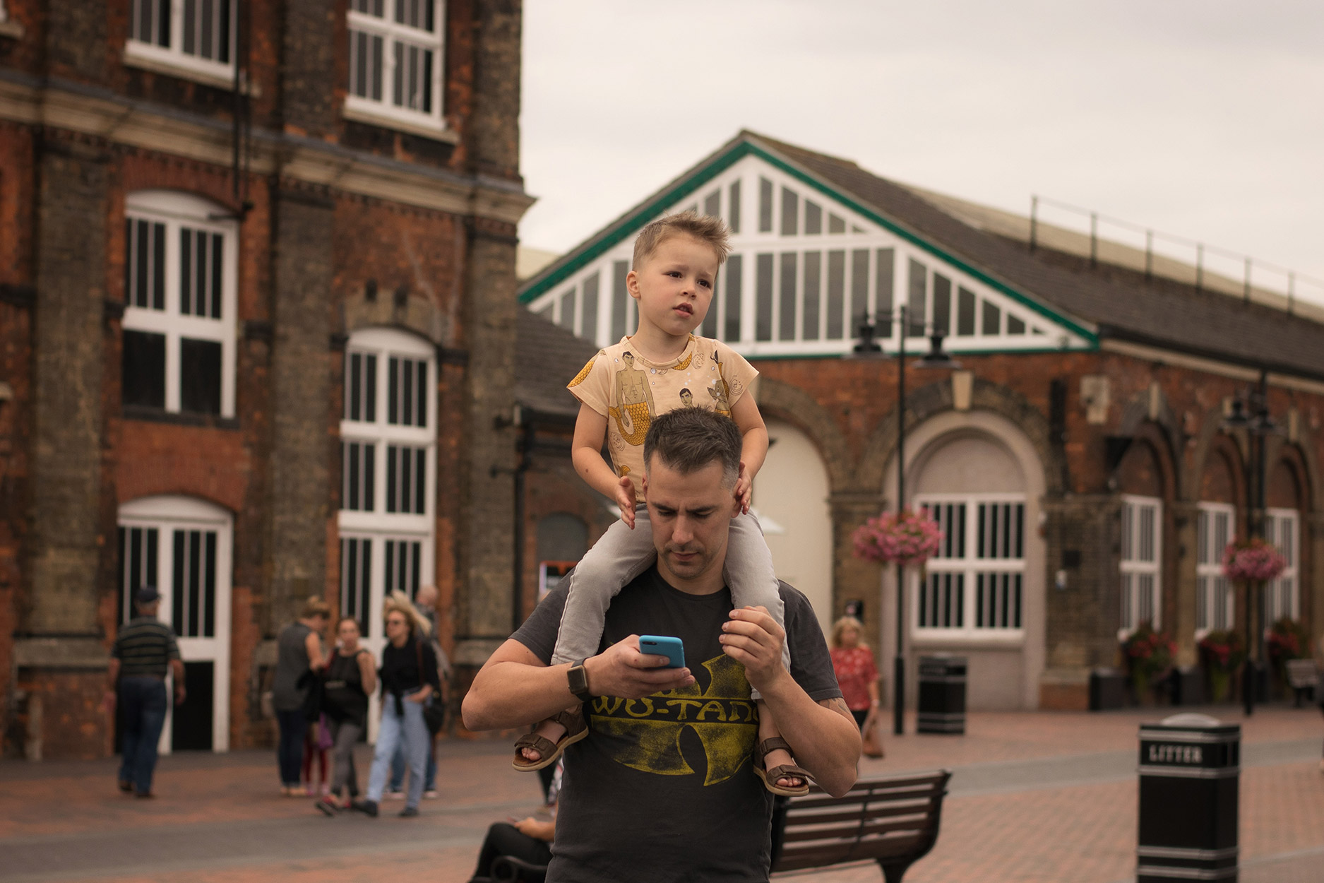 Boy wearing Mini Rodini mercies t-shirt on Dad's shoulders going to Wagamama's for dinner