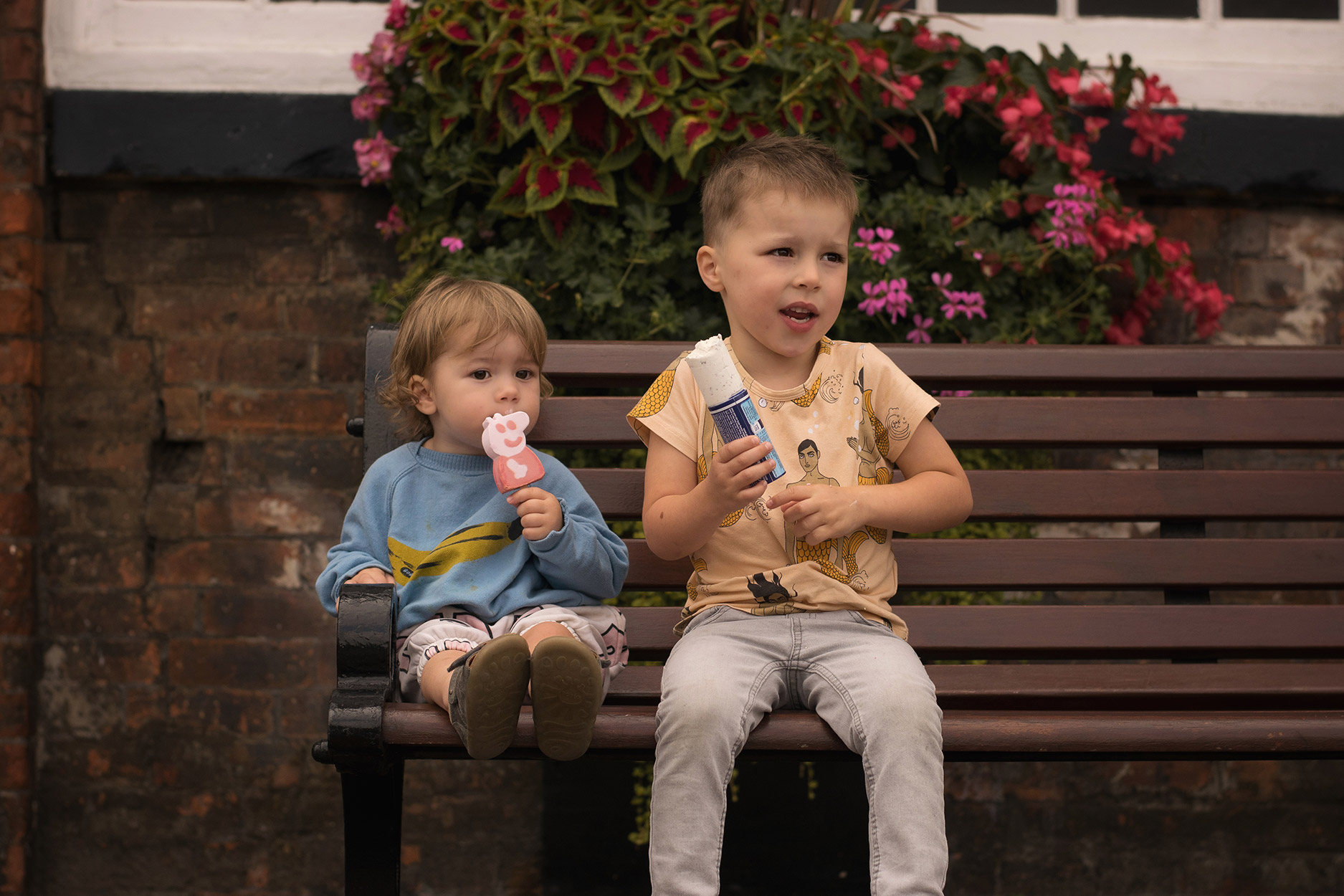 Brothers wearing Bobo Choses bananas, Mini Rodini mercies and Hugo Loves Tiki rad shorts eating Peppa Pig ice-cream sitting on bench