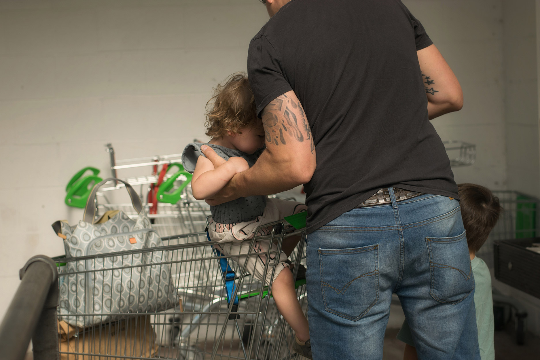 Dad taking boys shopping in trolley