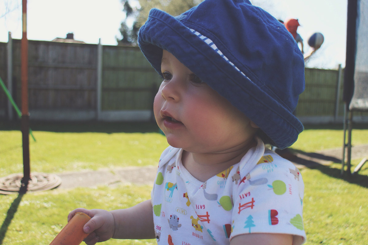 An Easter Weekend Catch-Up - Toddler staring up wearing sunhat on Easter Monday at family BBQ