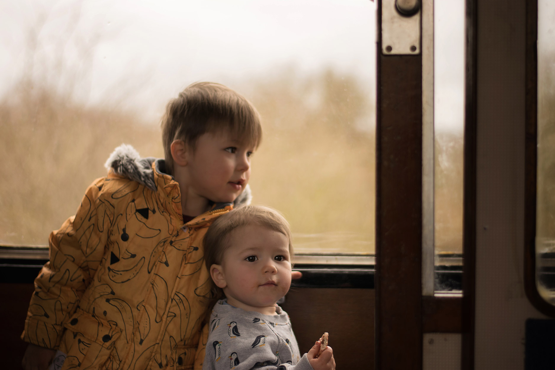 Young family of two boys and grandparents on the Blunsdon and Cricklade railway for the Easter Eggspress, playing in the old steam train carriages and wearing Frugi penguins and Milk & Biscuits moon sweatshirt