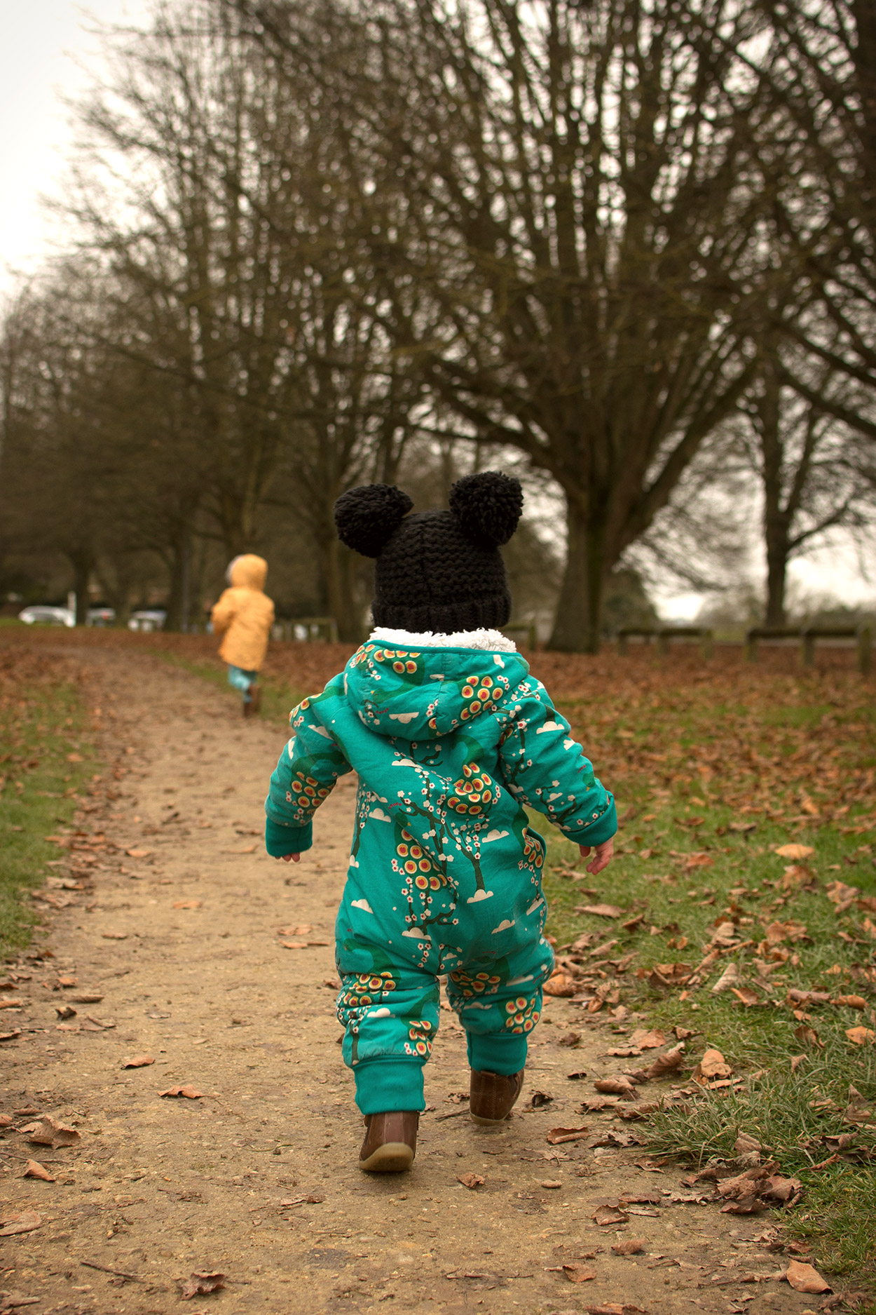 Mum, Dad and two young brothers, toddler and pre-schooler, dressed in Little Green Radicals midnight peacocks snowsuit, Individual banana print parka coat, Bobux iWalk outback boots and having a family portrait in the woods, Wiltshire