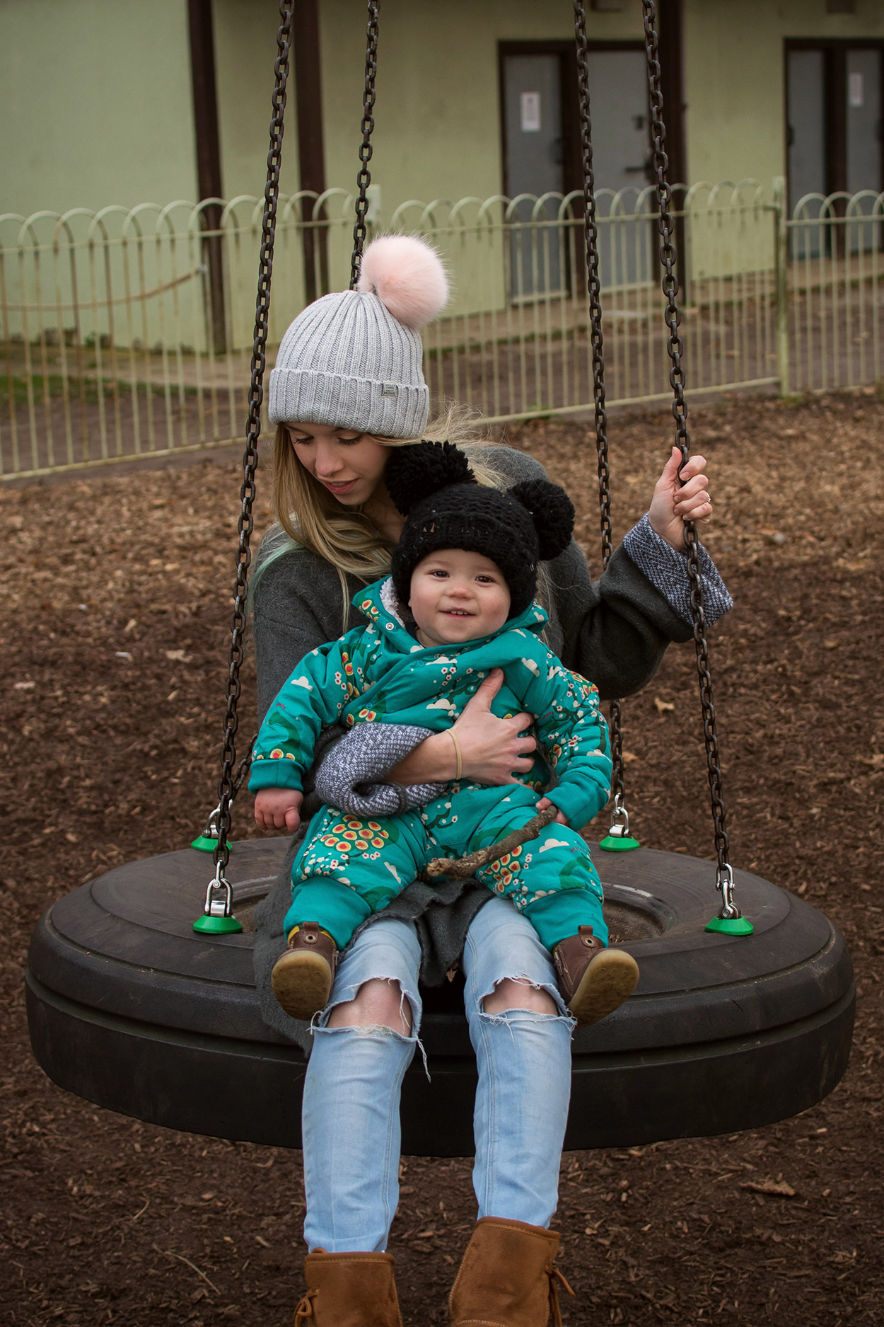 Young toddler sitting on Mothers lap on the swings at the park in Autumn