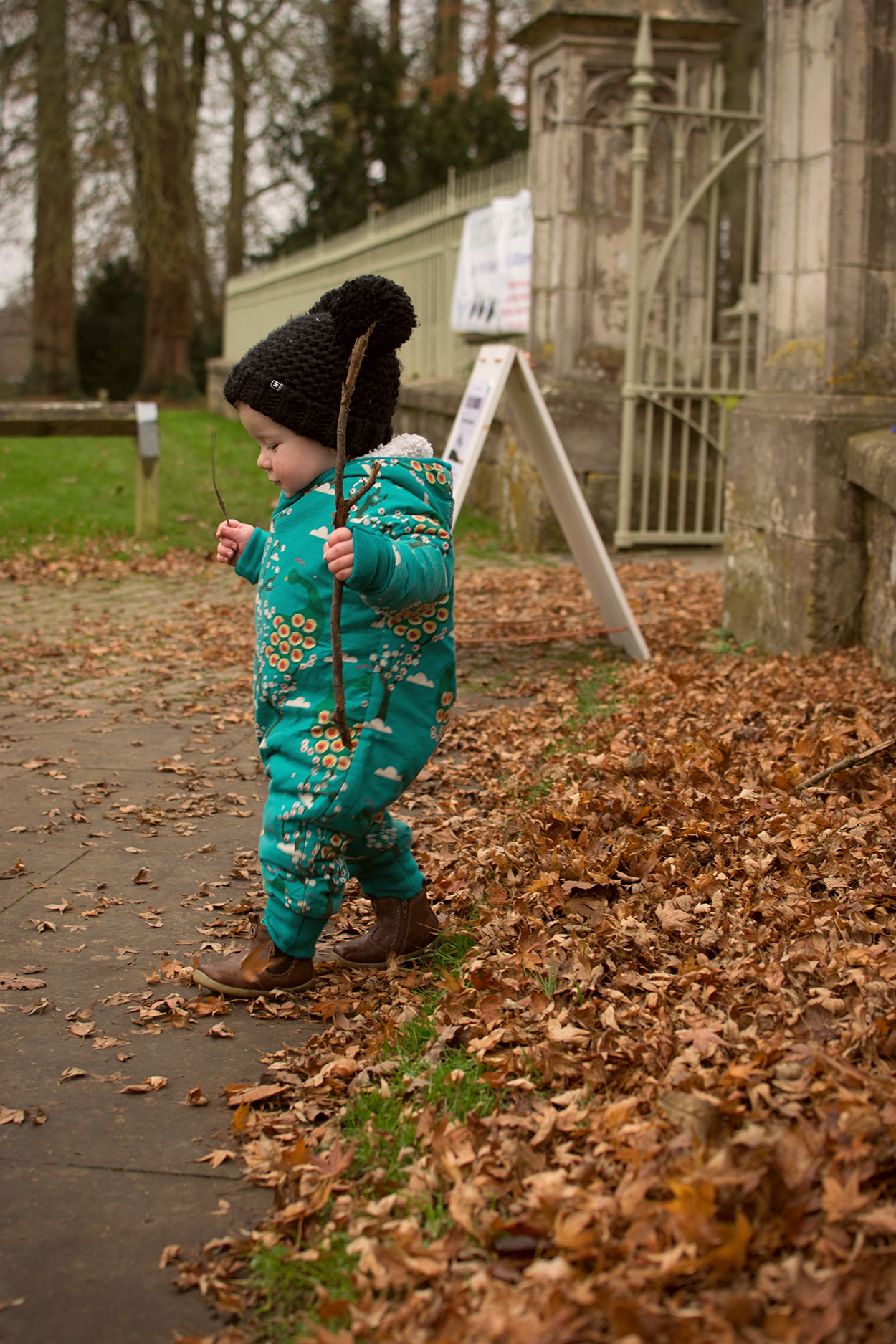 Young toddler wearing Little Green Radicals snowsuit and MyK wooly hat brandishing a stick walking through the Autumn leaves at the park