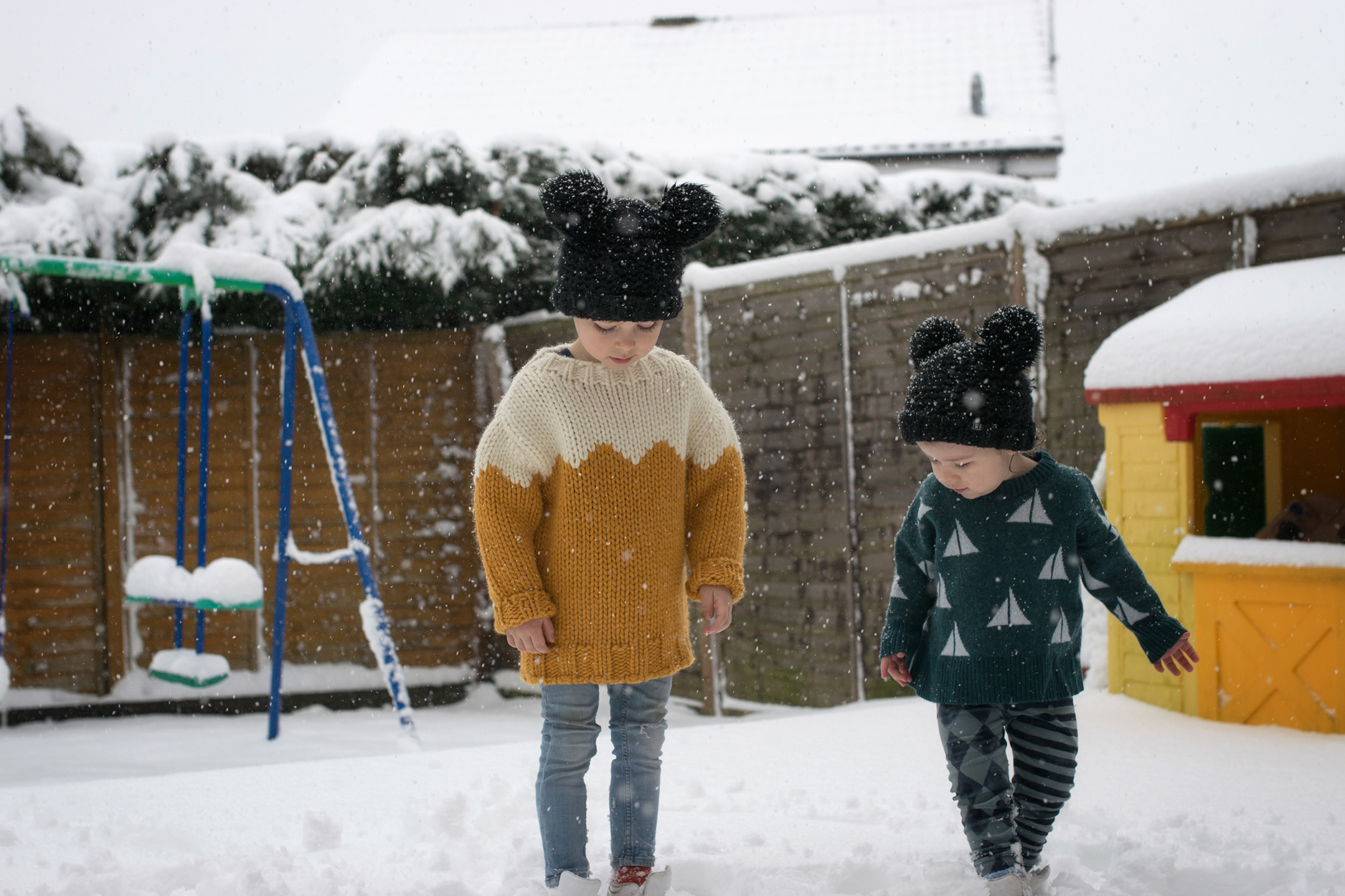 Family including two brothers playing in snow blizzard wearing Mini Rodini K2 penguins, Rylee and Cru fur and Individual banana snowsuit